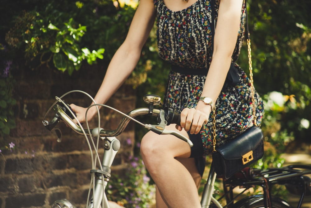 woman riding on commuter bike during daytime