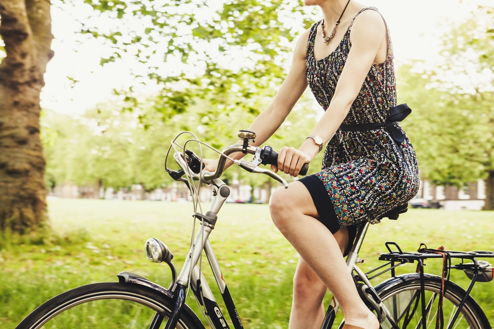 woman riding bicycle near grass