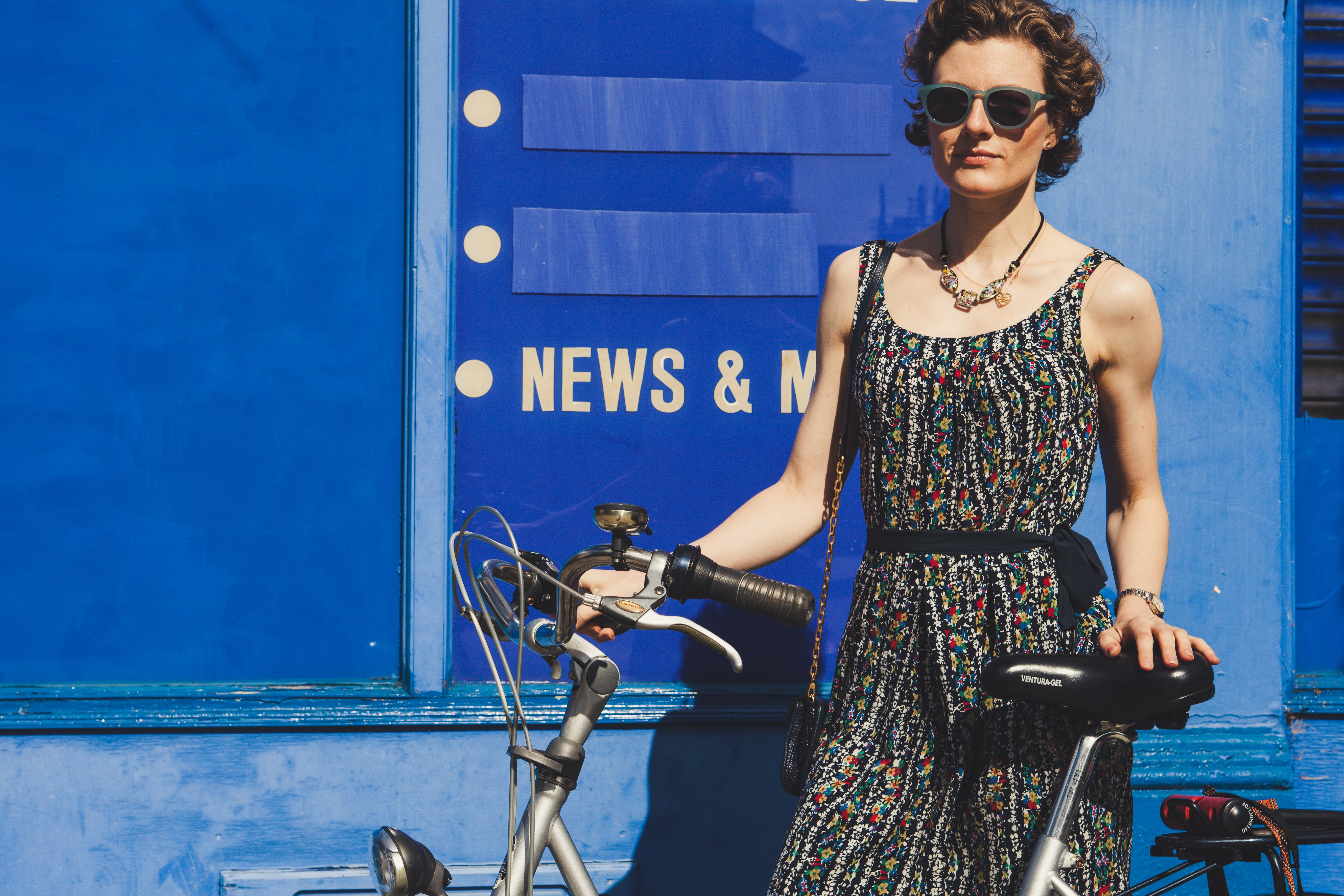 A woman wearing a floral print dress on a sunny day standing against a blue wall, holding her bicycle, in London
