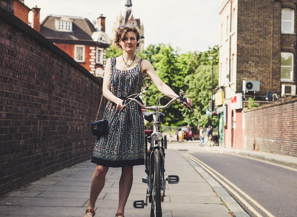 woman holding bicycle beside wall bricks