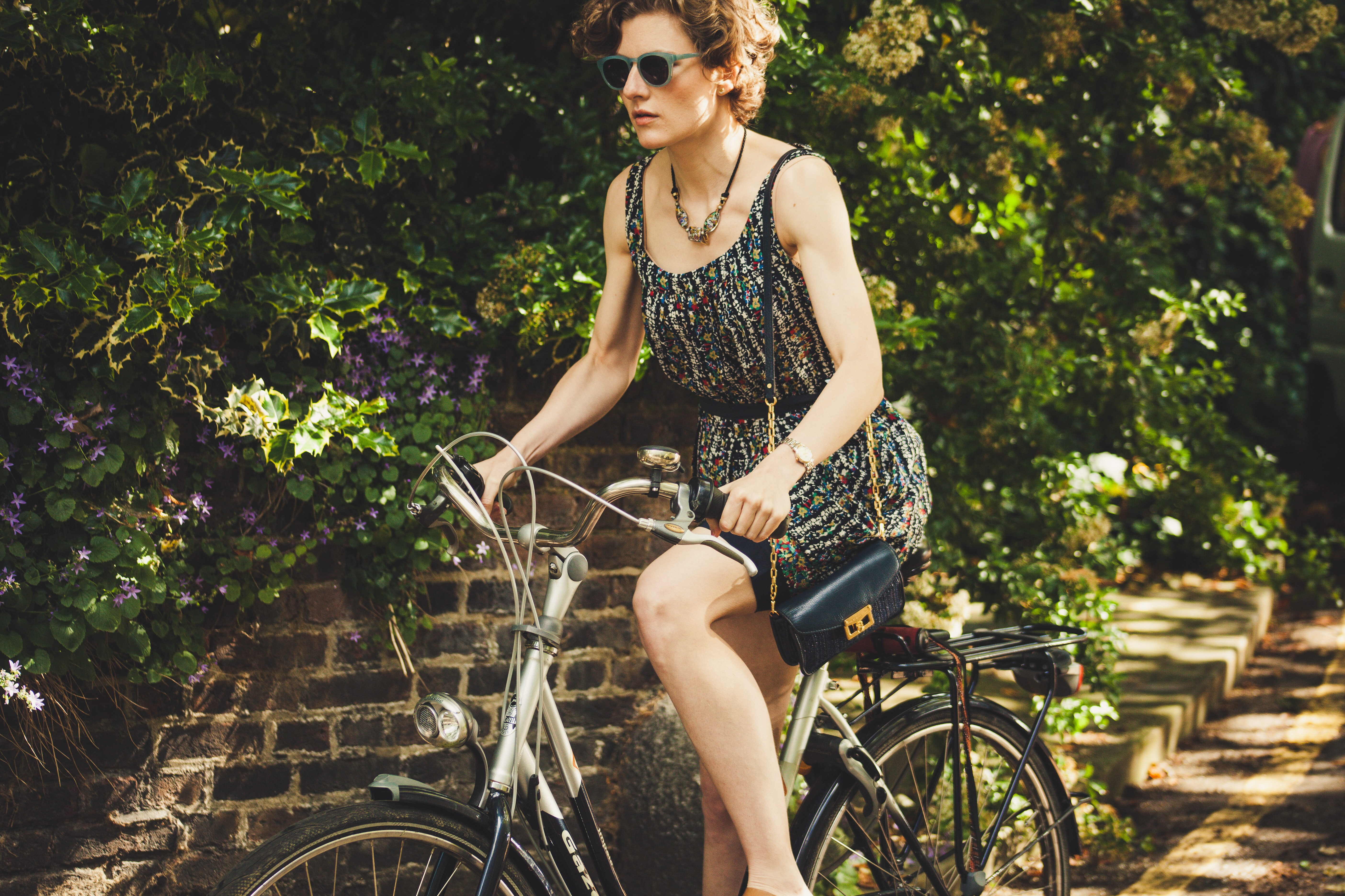 Woman wearing gold watch, dress, and purse and riding vintage bike through London