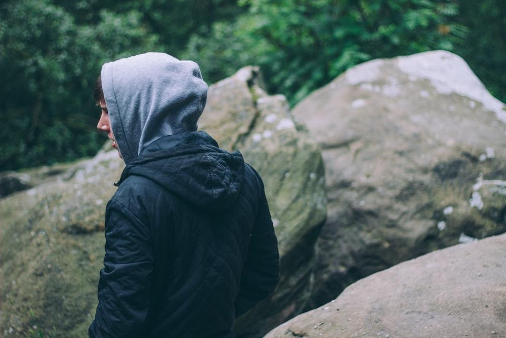 person in black hoodie near gray rocks