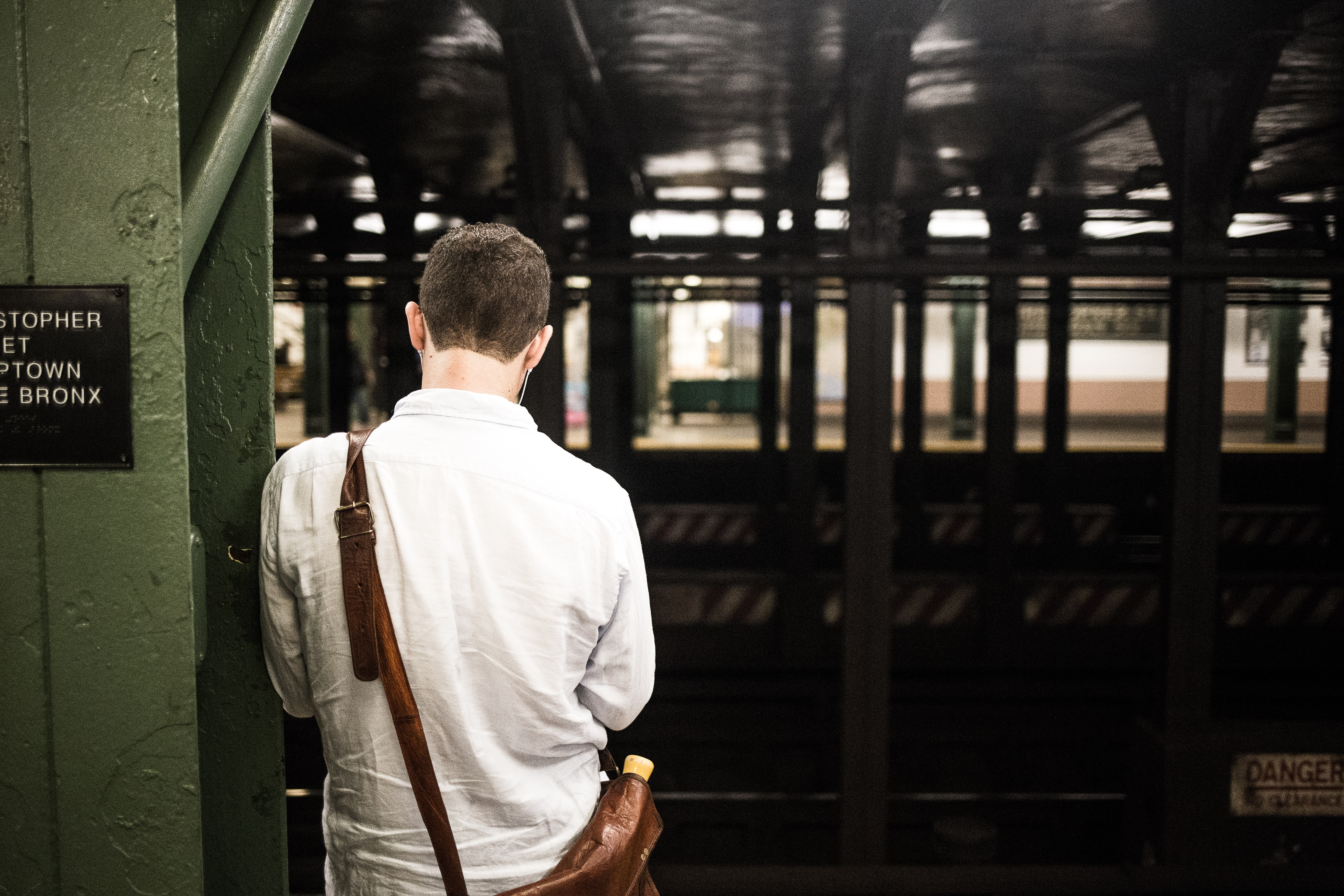 Man leaning up against a post waiting for a New York subway to the Bronx