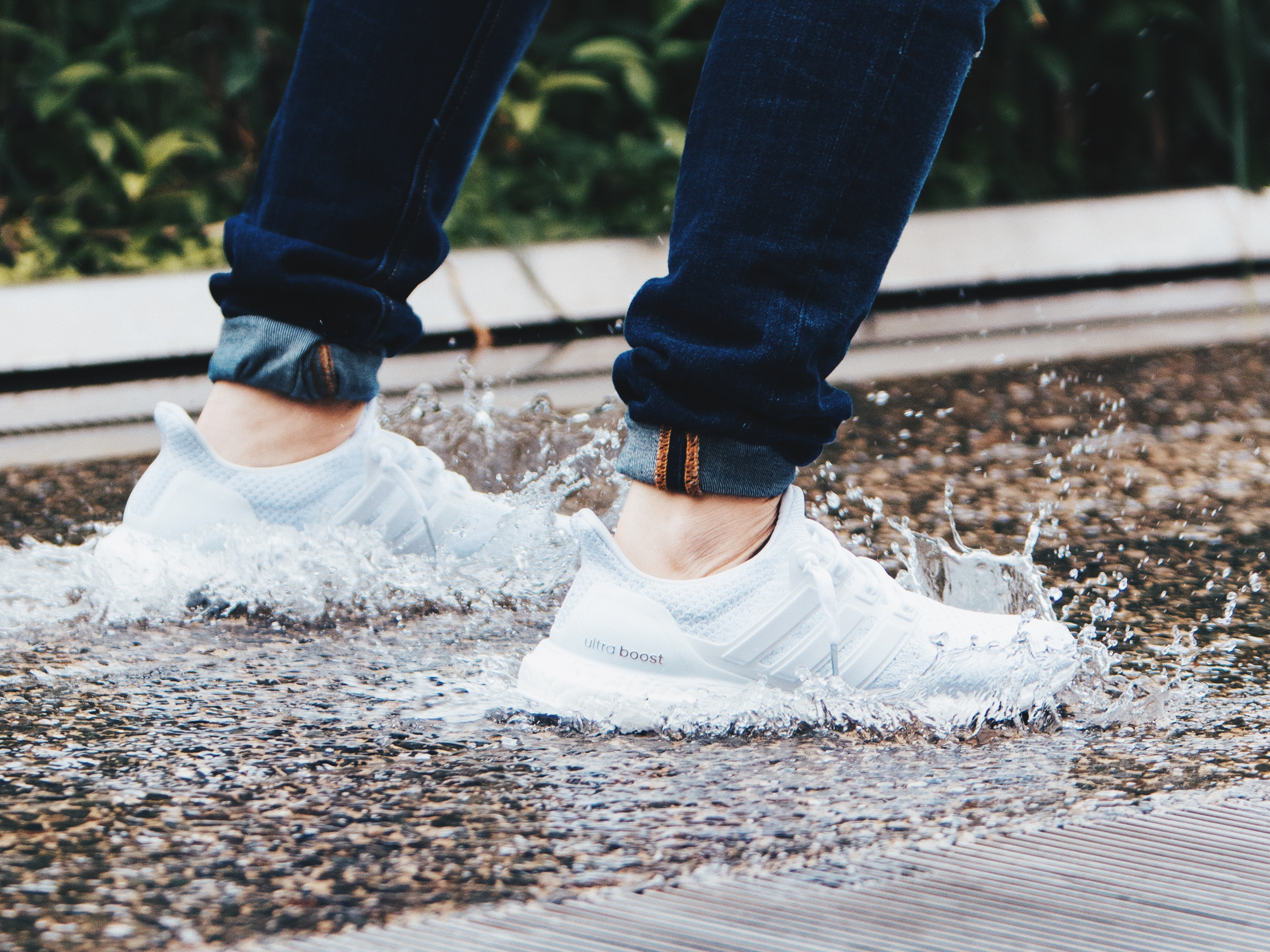 person wearing pair of gray adidas UltraBOOST low-top sneakers stepped on pool of water