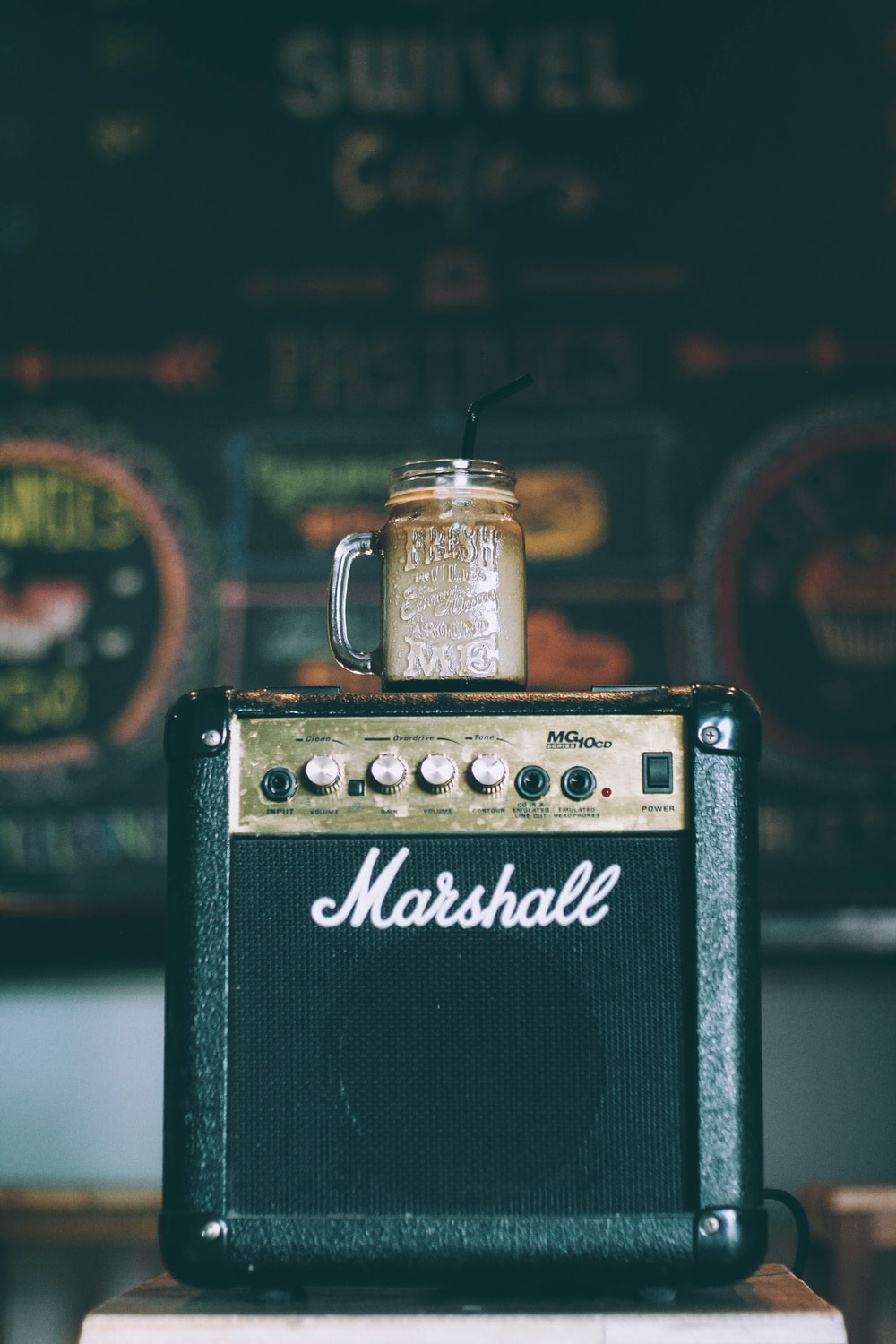 black Marshall guitar amplifier with glass mug on top filled with beverage