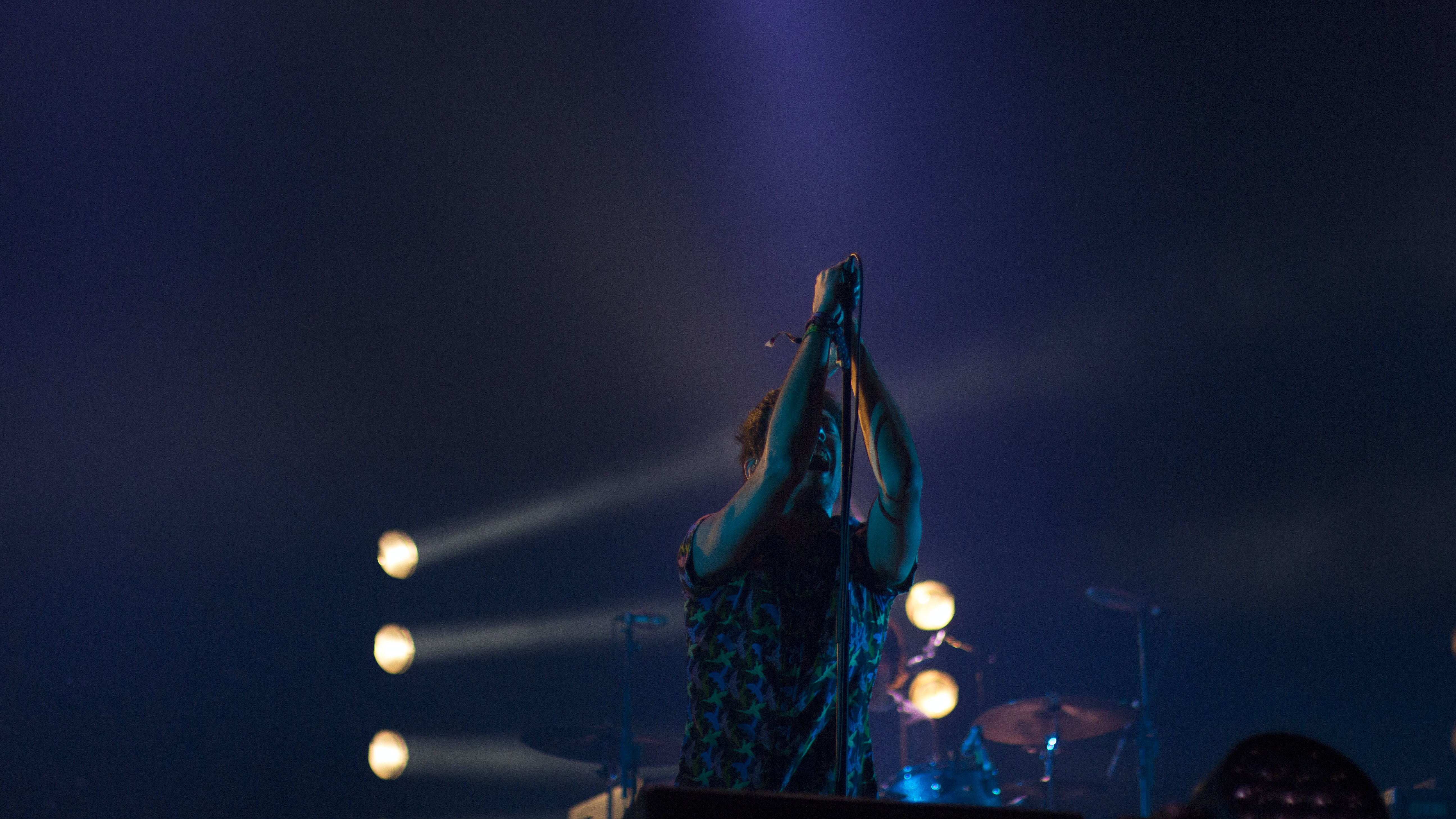 A vocalist singing into a microphone on a stand pointed downwards