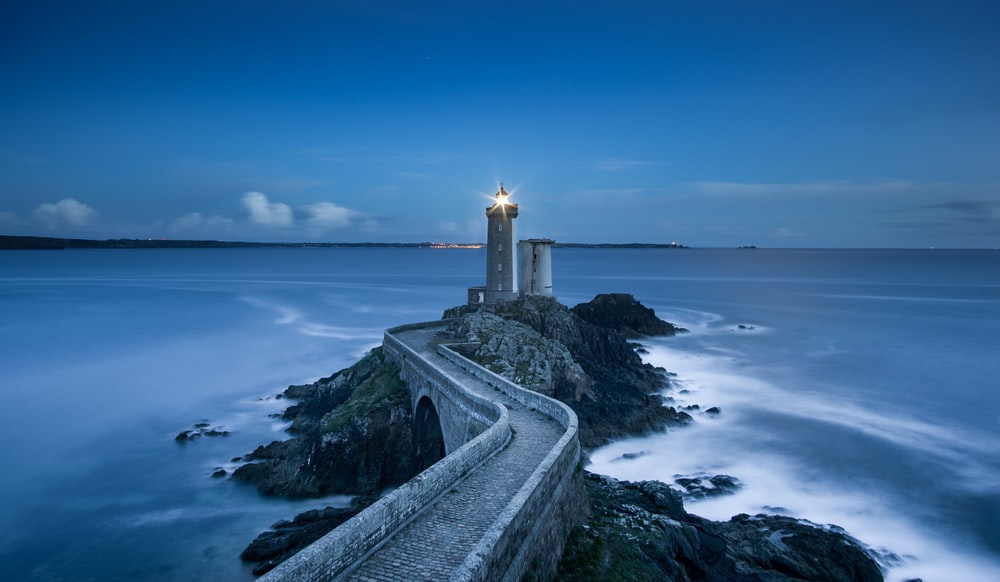 gray lighthouse on islet with concrete pathway at daytime