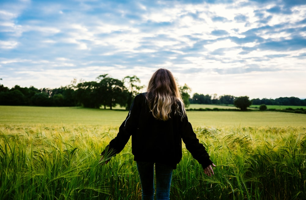 woman walking on grass field during daytime