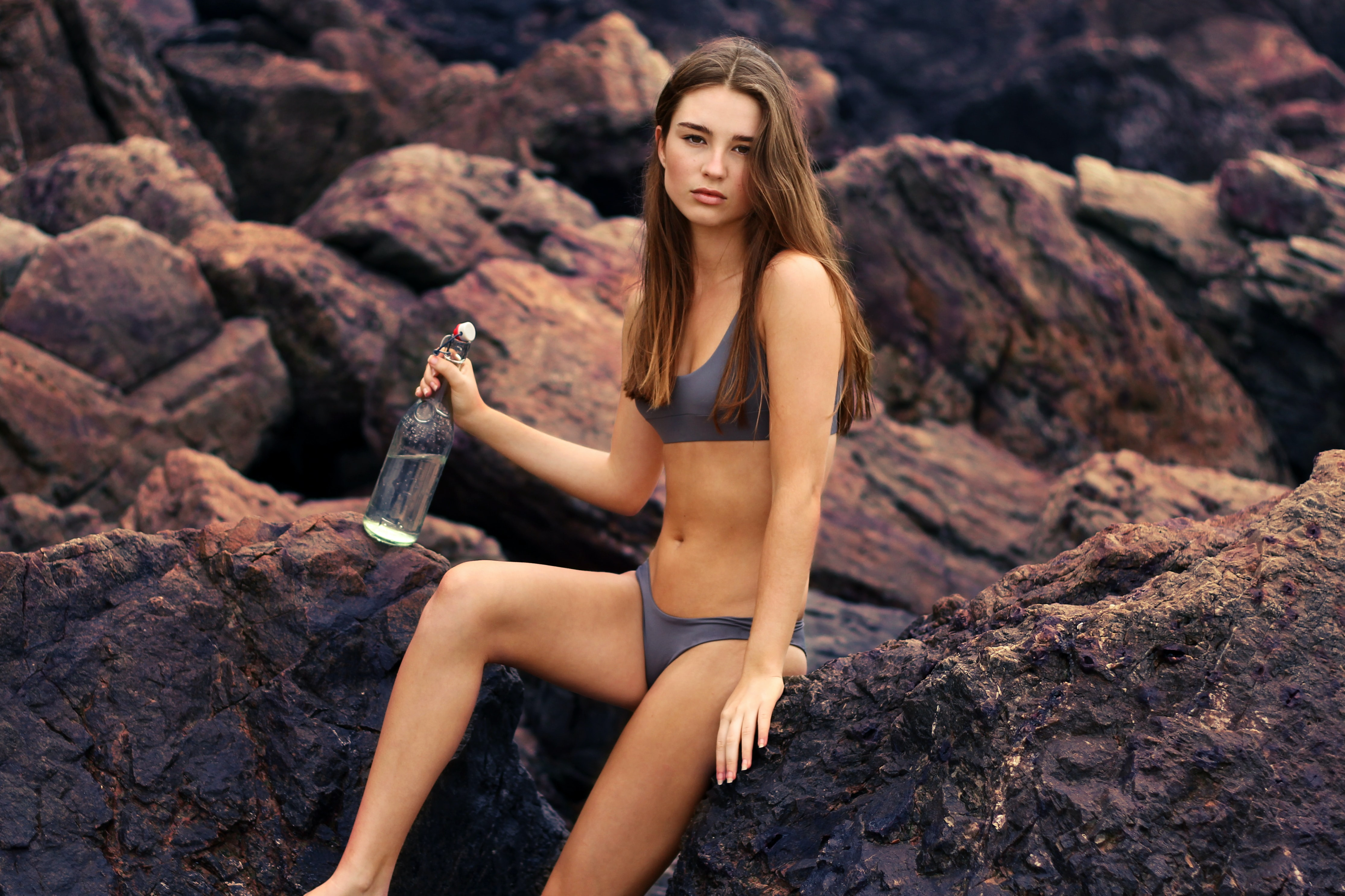 A brunette woman wearing a grey bikini, holding a bottle of water whilst sitting on rocks at North Burleigh Surf Life Saving Club