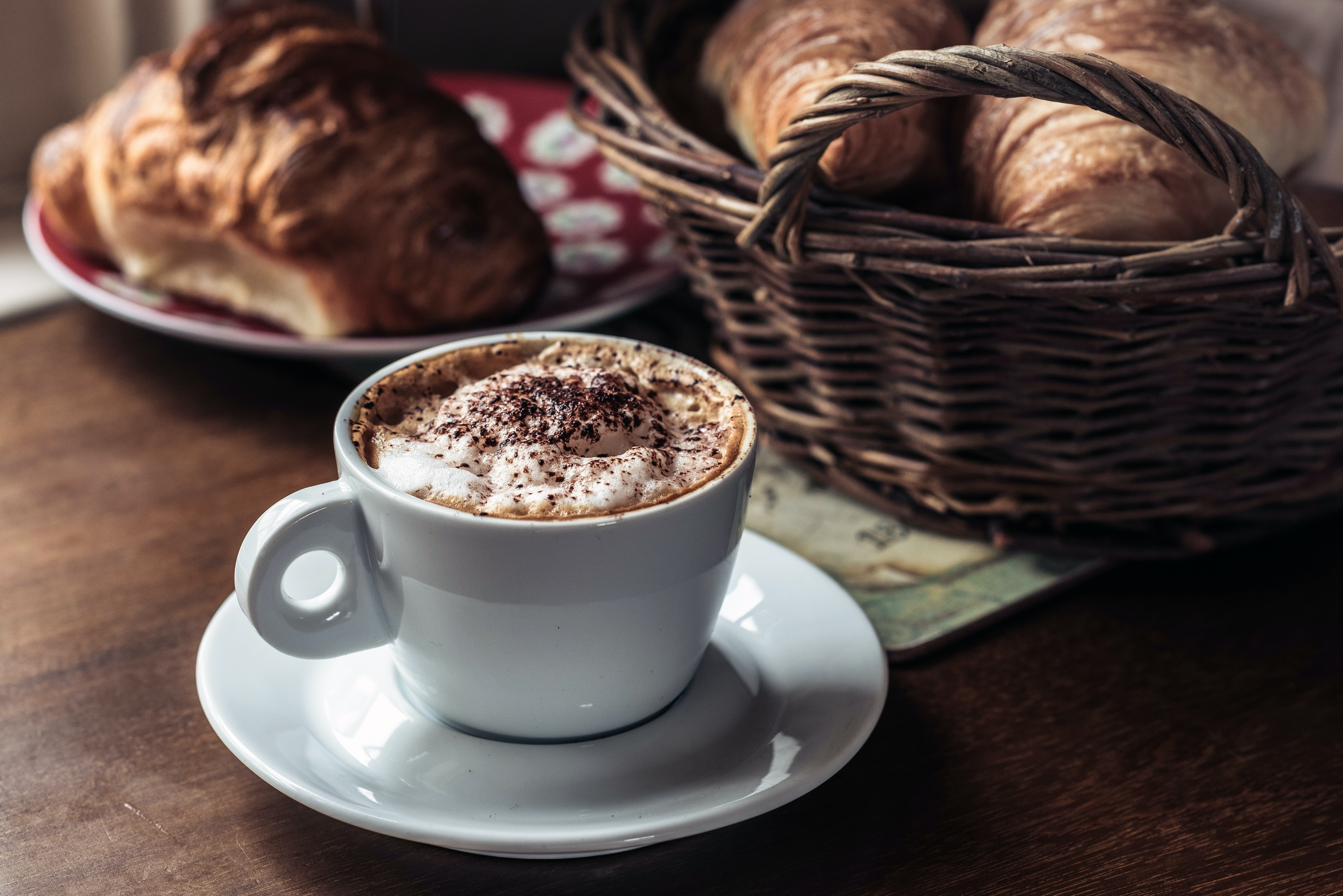 capuccino coffee on white ceramic cup with saucer beside pastry bread in basket and red plate