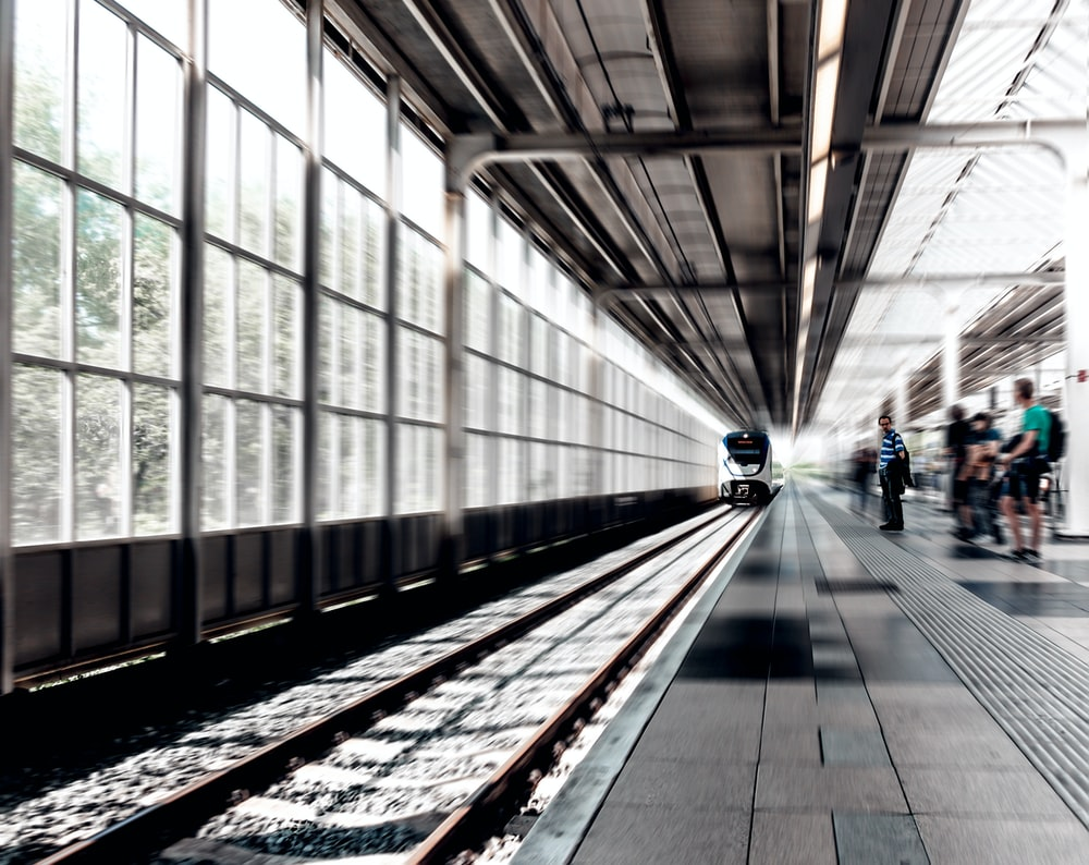 time lapse photo of train running on train station with people beside during daytime