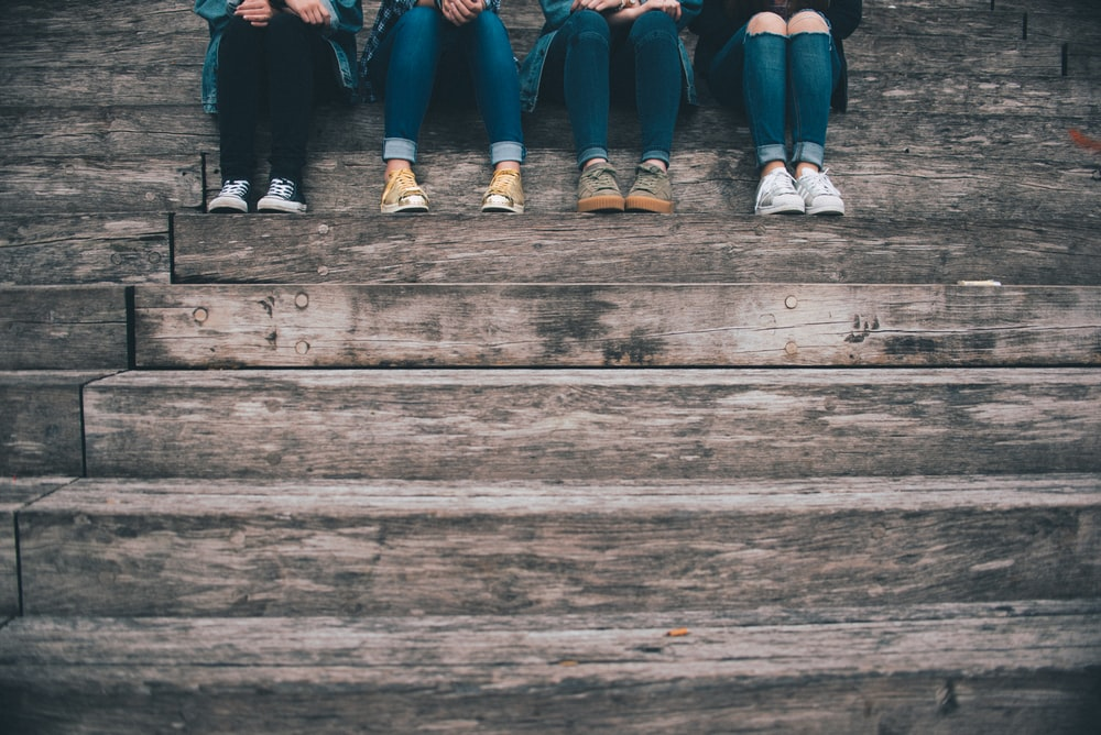 four people sitting on wooden stair