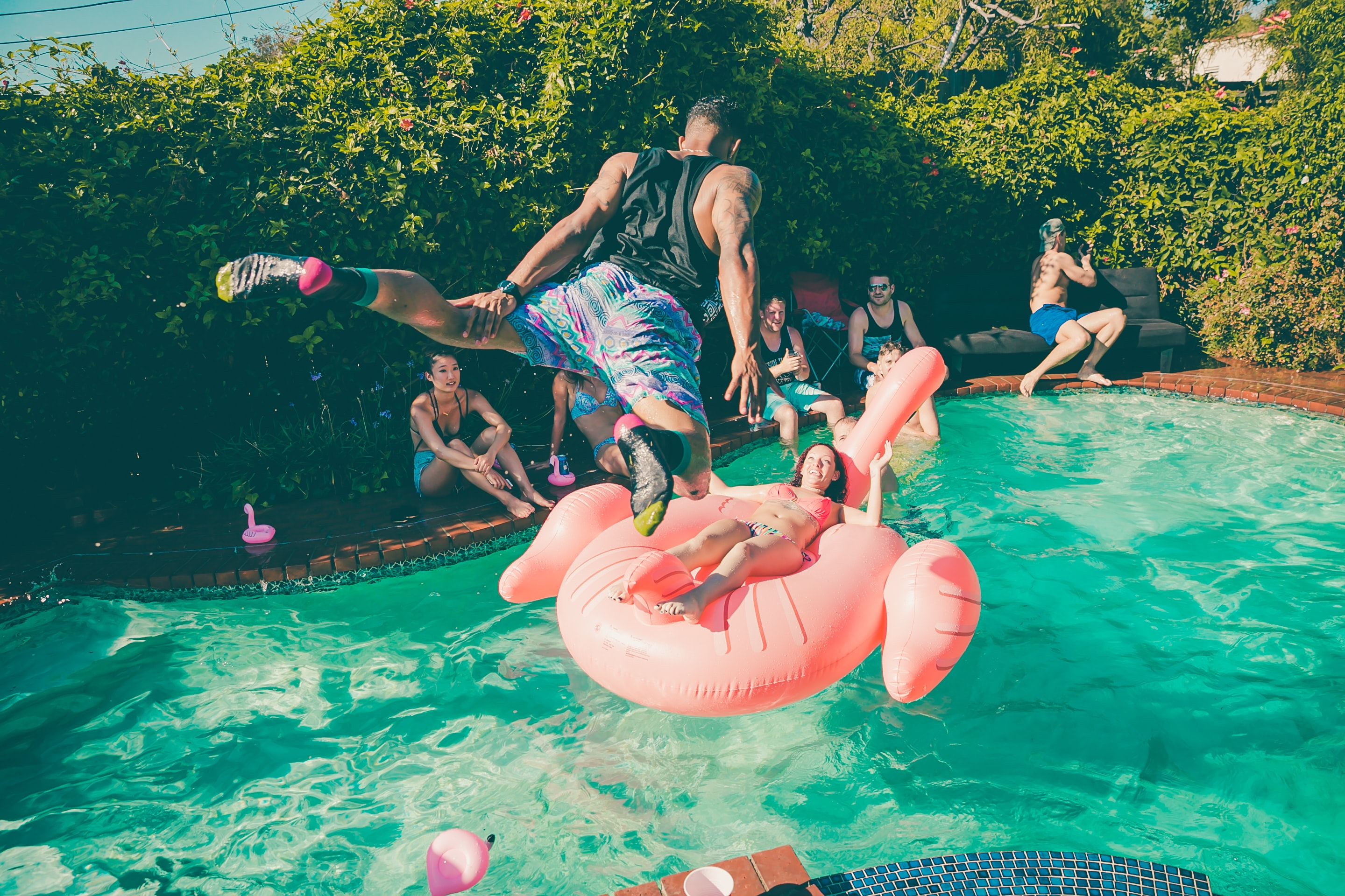 A man diving into a pool at a party.
