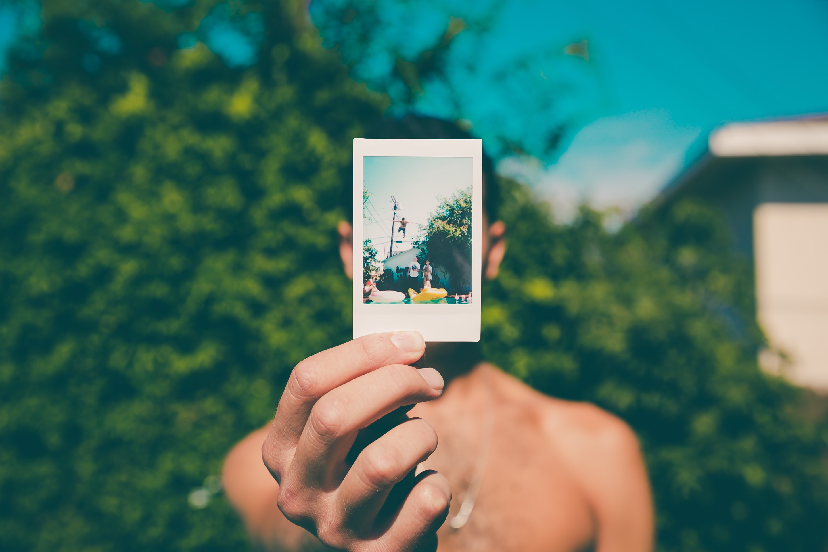topless man holding photo of person diving on pool selective focus photography