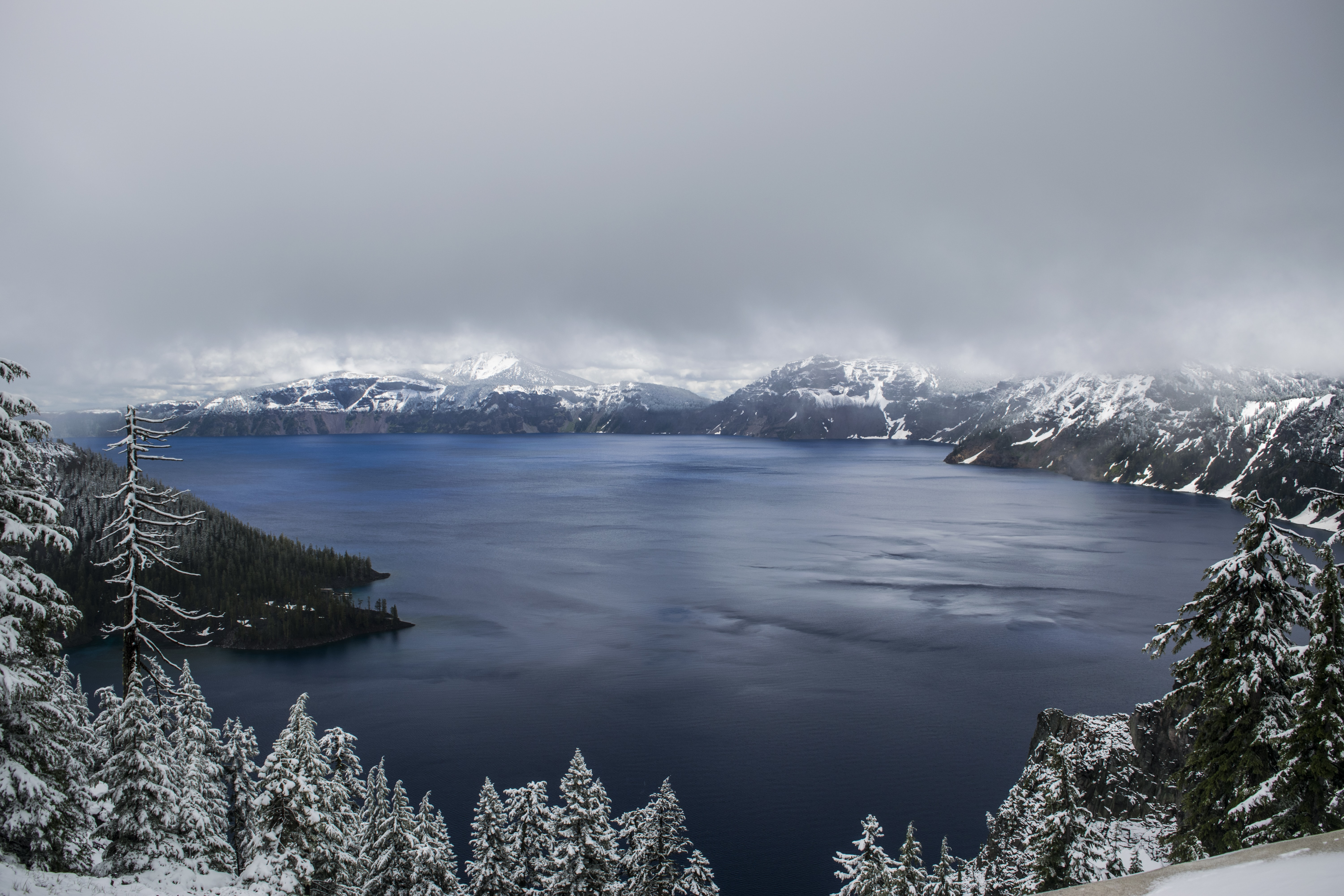 Crater Lake with a frozen shoreline of trees under thick gray fog and clouds