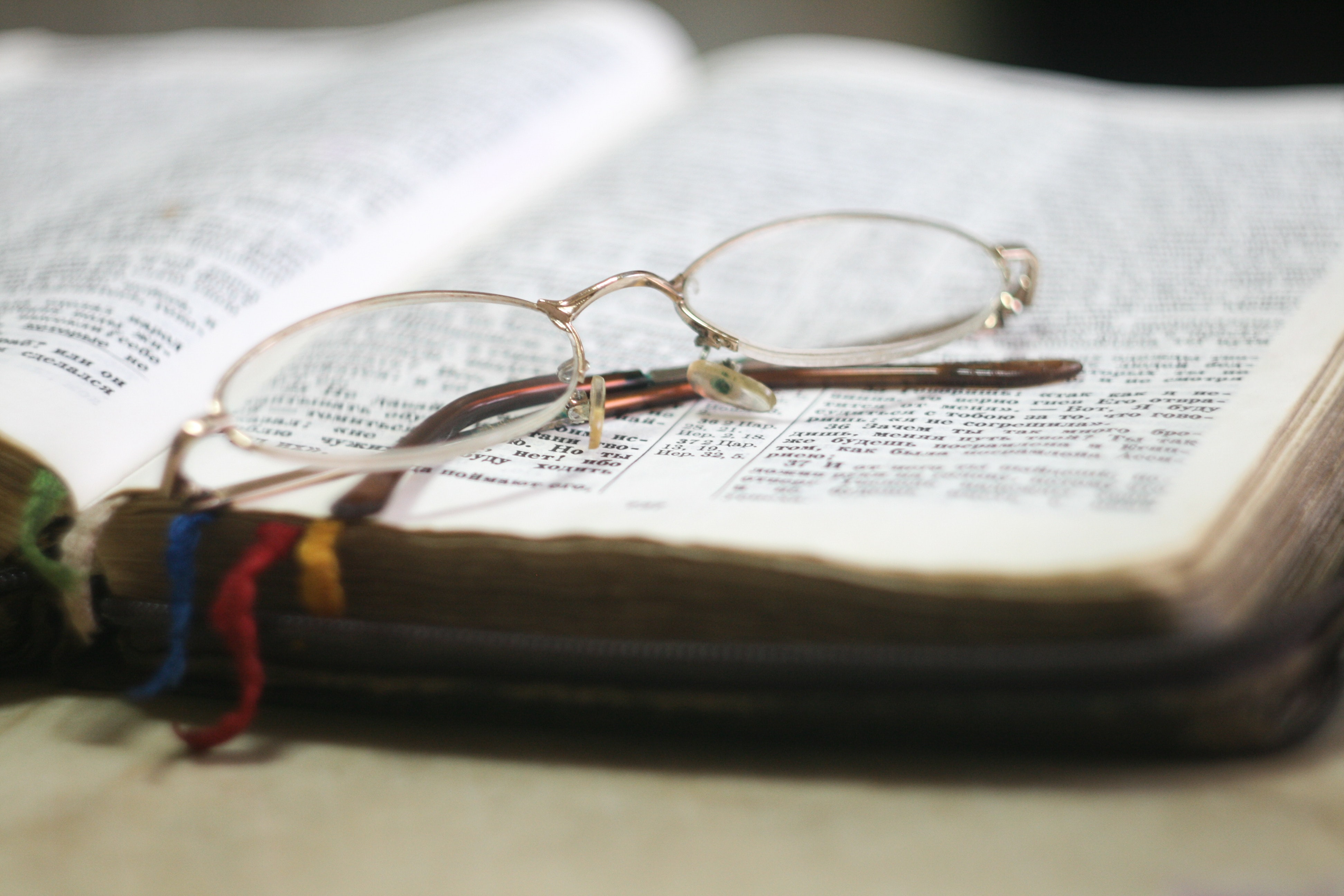 A pair of reading glasses on top of a book.