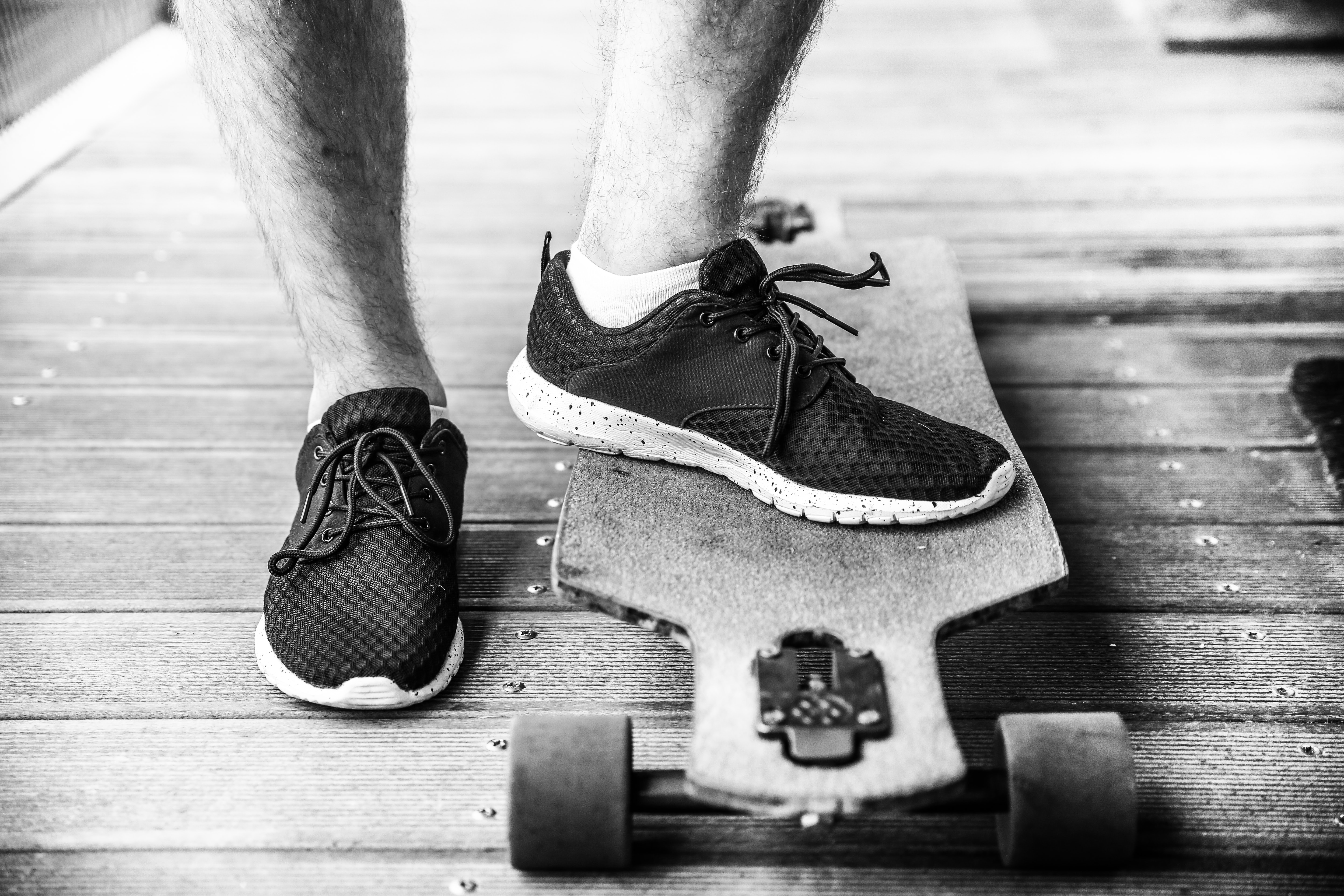 grayscaled photography of person on longboard