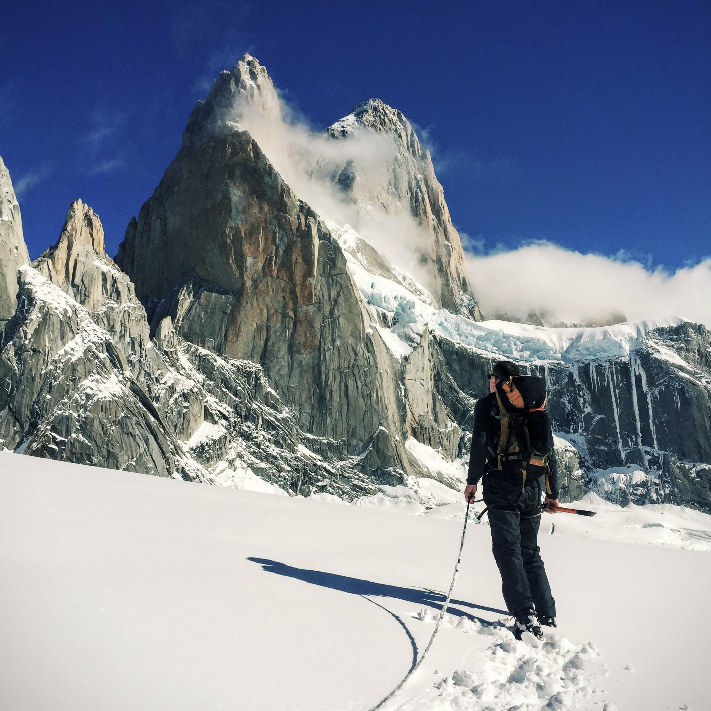 A man with mountaineering gear looks at a steep jagged peak on a snowy day