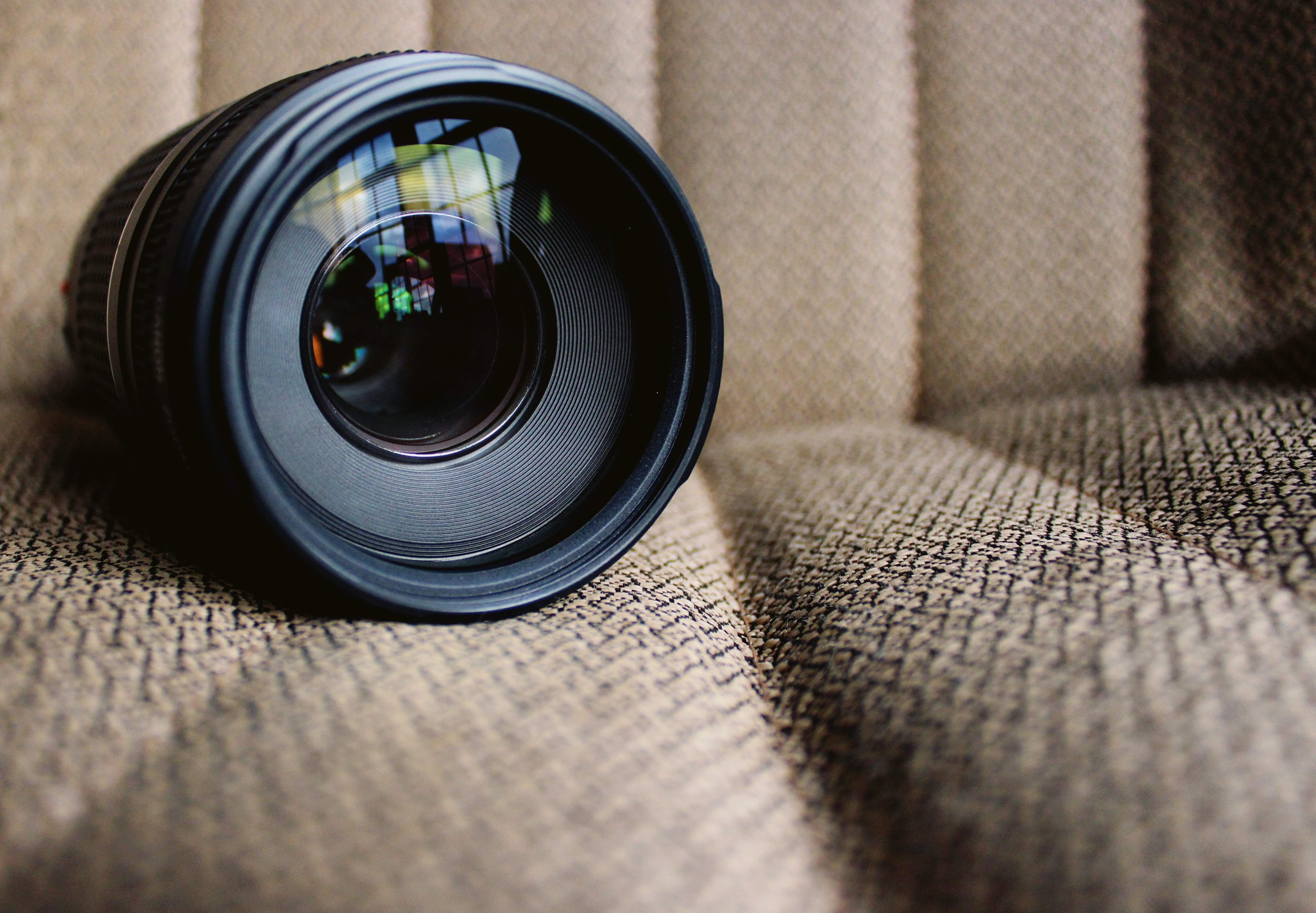 A close-up of a camera lens resting on the fabric texture of a chair.