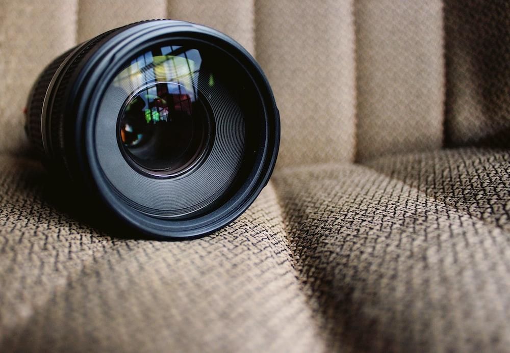 round black camera lens on brown fabric cushion
