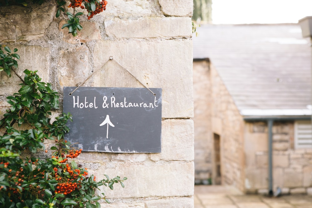 Hotel & Restaurant signage posted on concrete wall