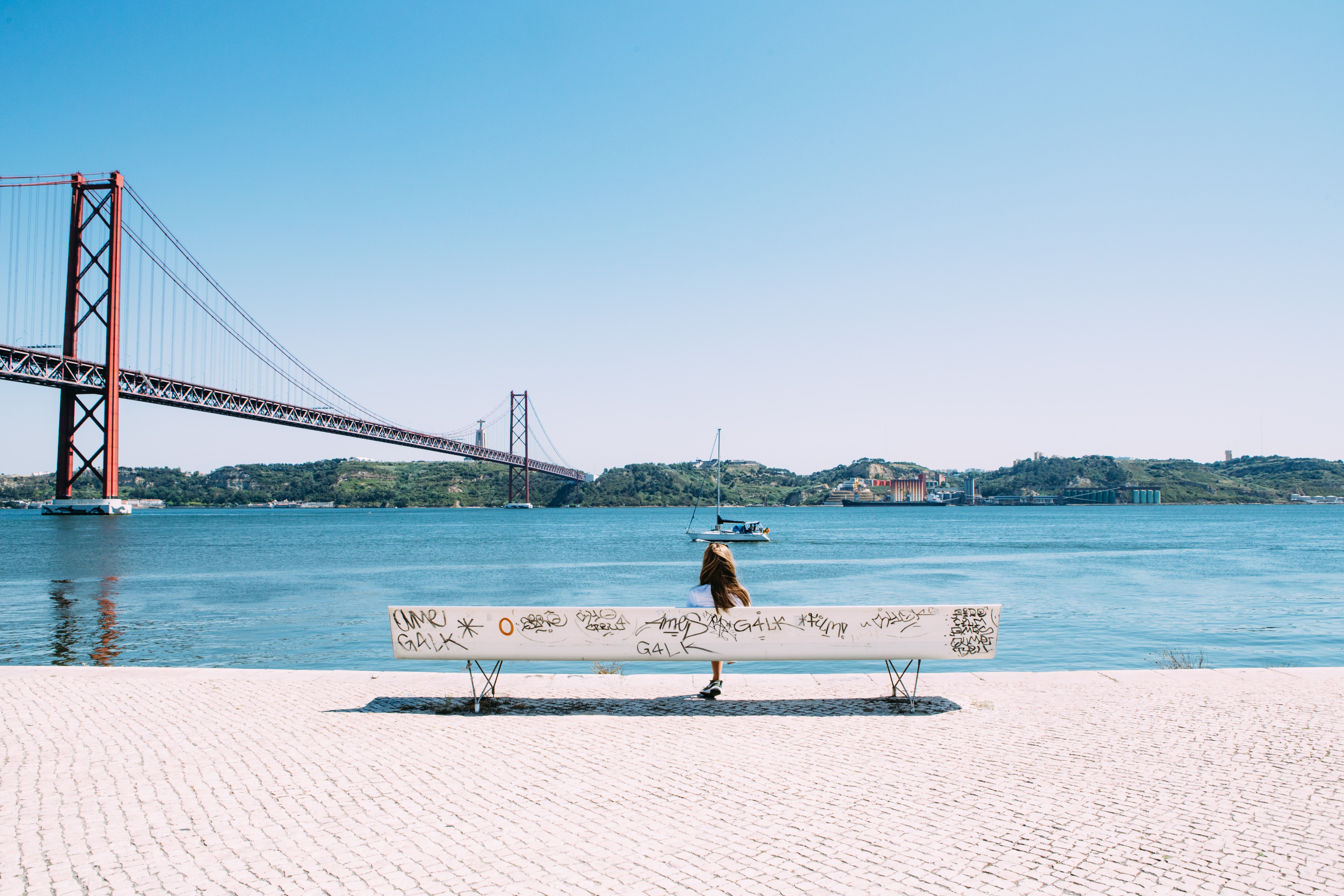 A woman sitting on a white bench with graffiti along the river in Lisbon