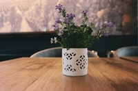 purple petaled flowers in white flower vase located on brown wooden table