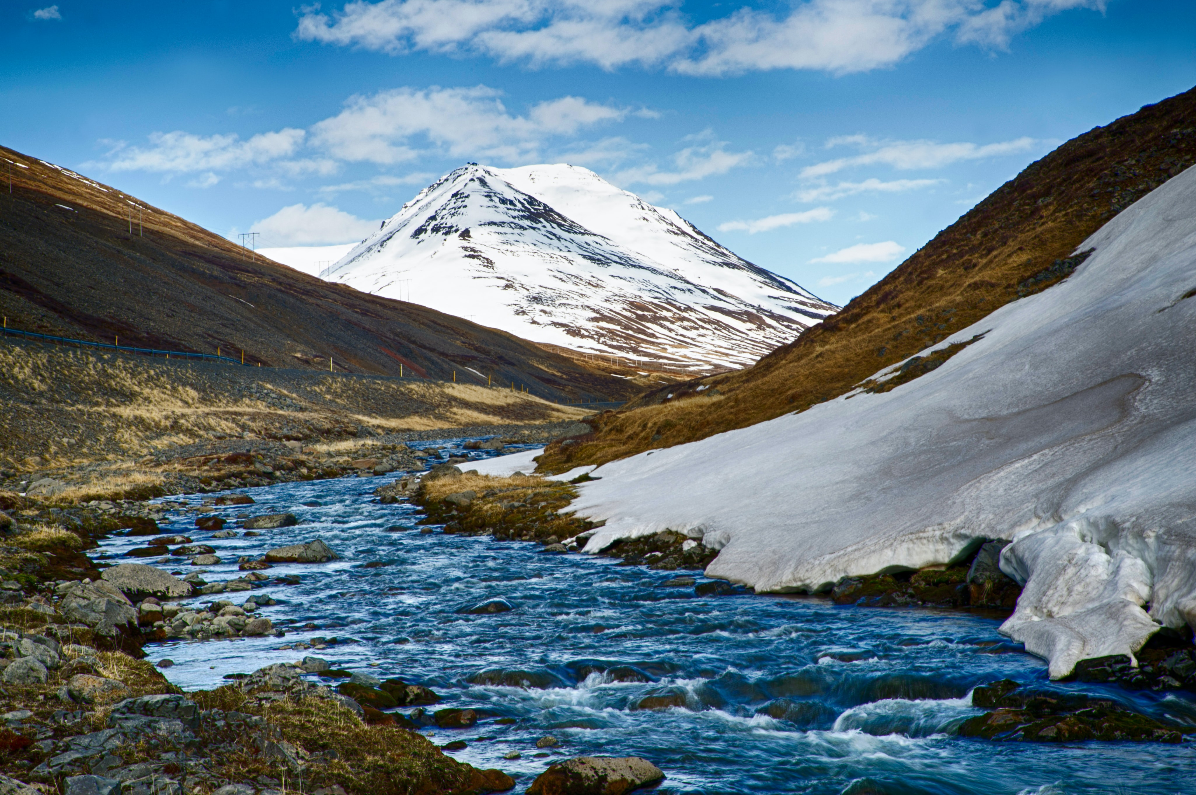 A river in a valley on Iceland is flowing in the direction of a snowy mountain
