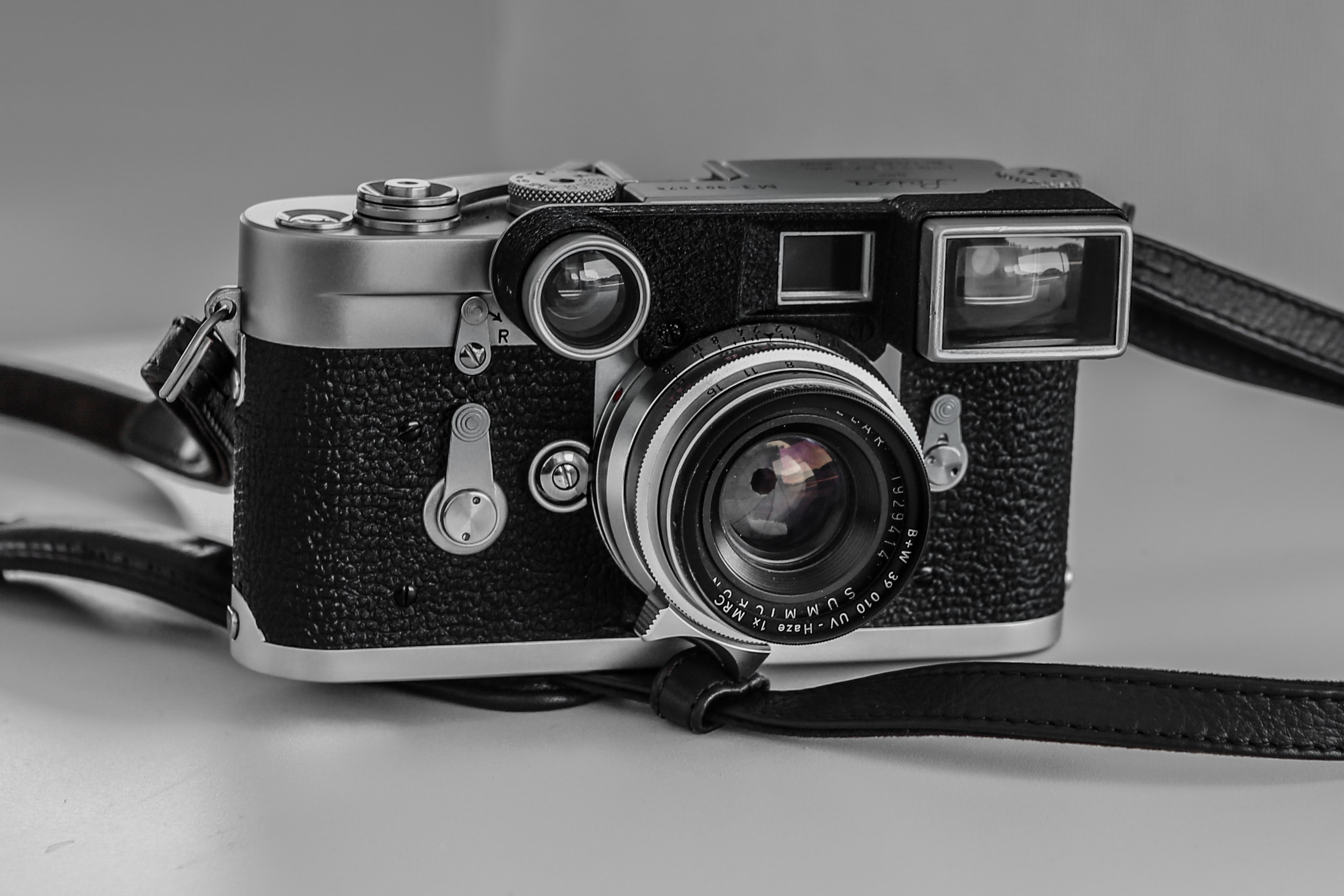 Vintage camera with leather black strap on a white surface