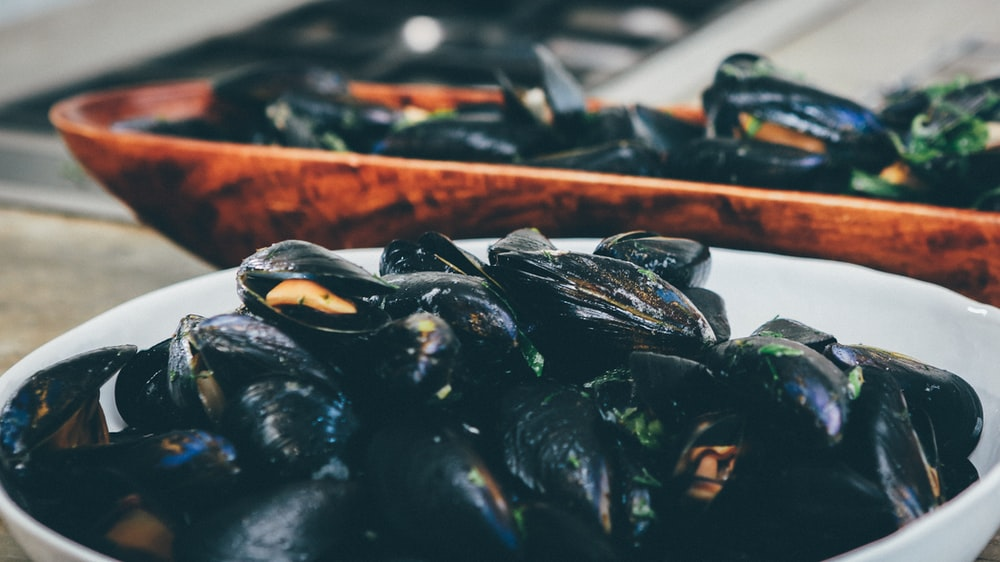 cooked mussel. in white bowl