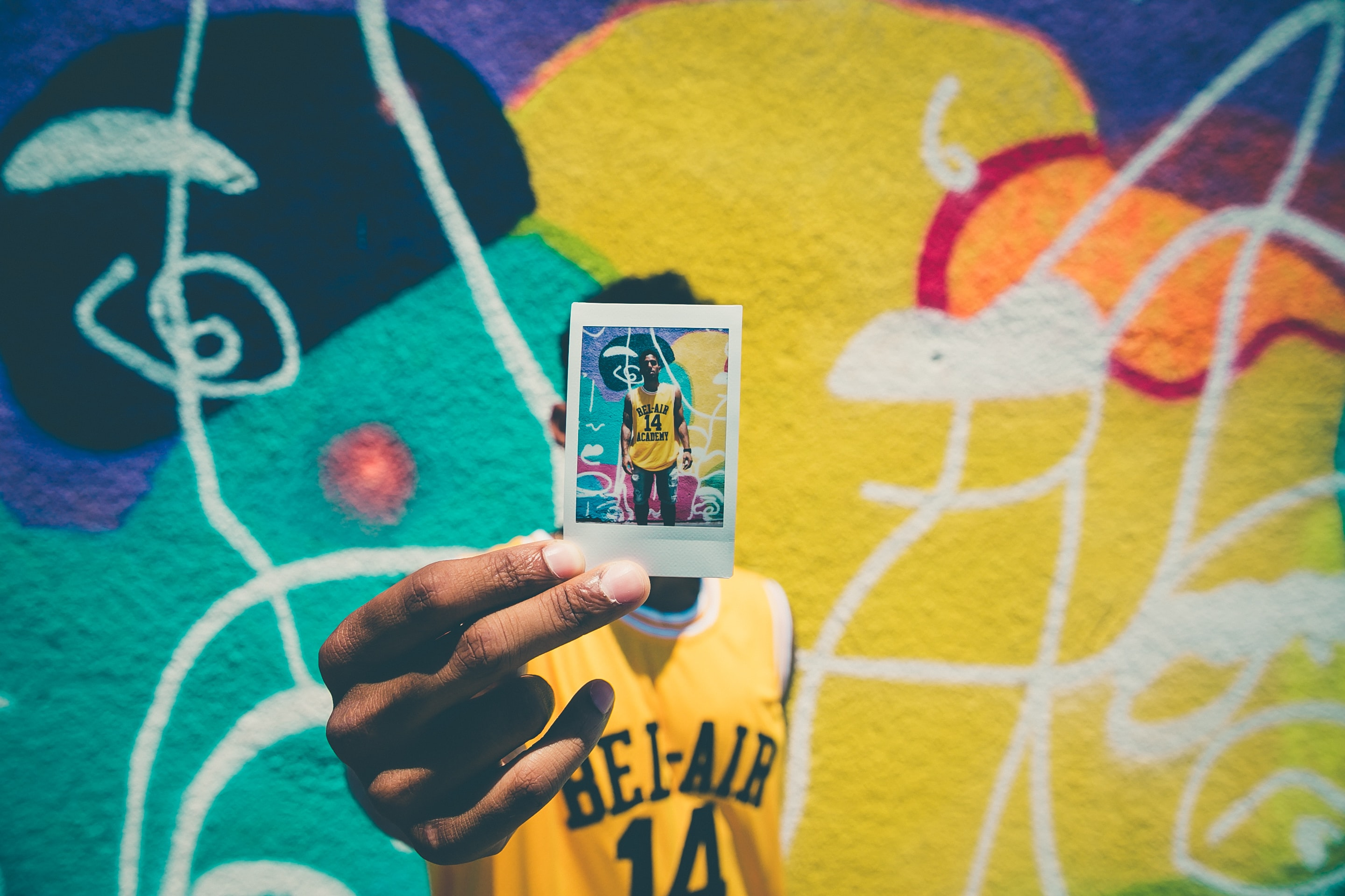 person holding printed photo of him with graffiti as background