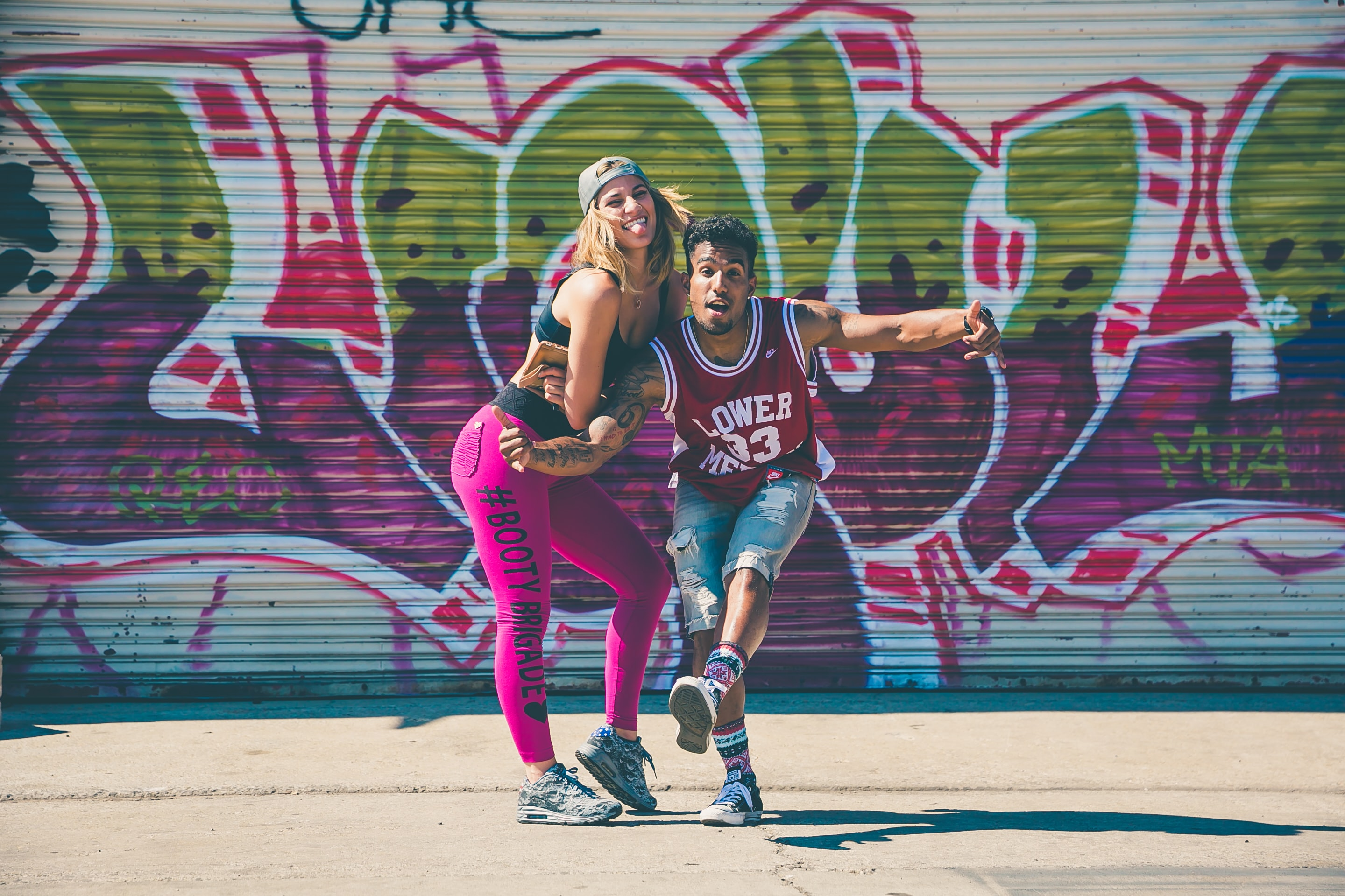 A girl and guy acting goofy and dancing in front of a graffiti wall