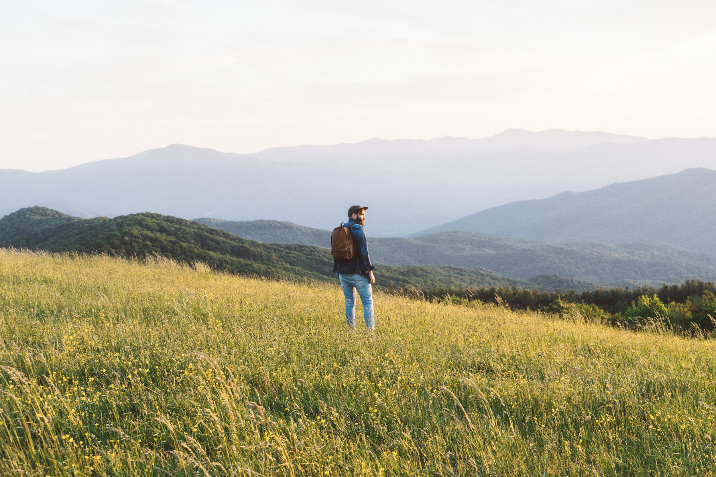 man standing on grass field in mountain