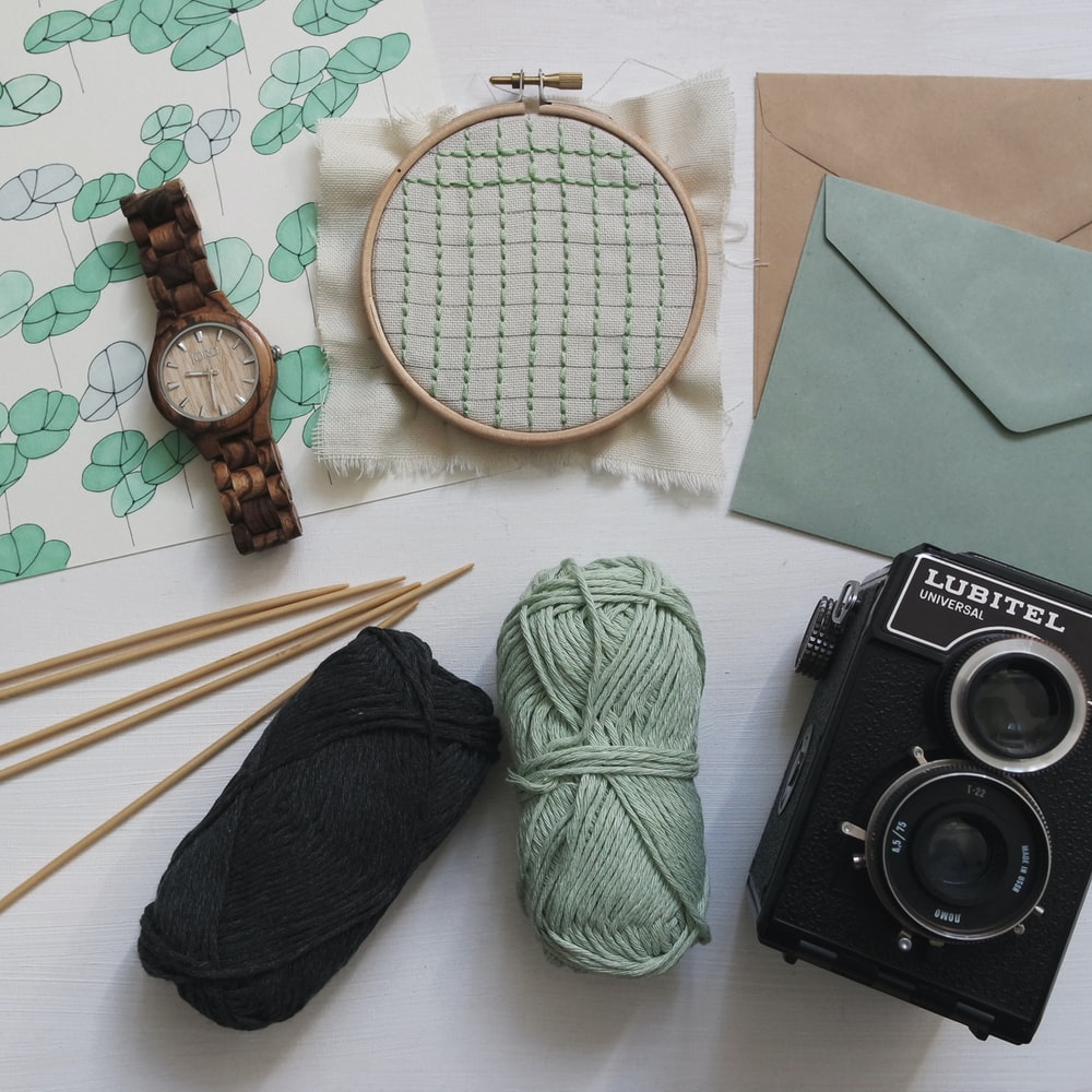 green and black yarns with round brown watch and black Lubitel camera