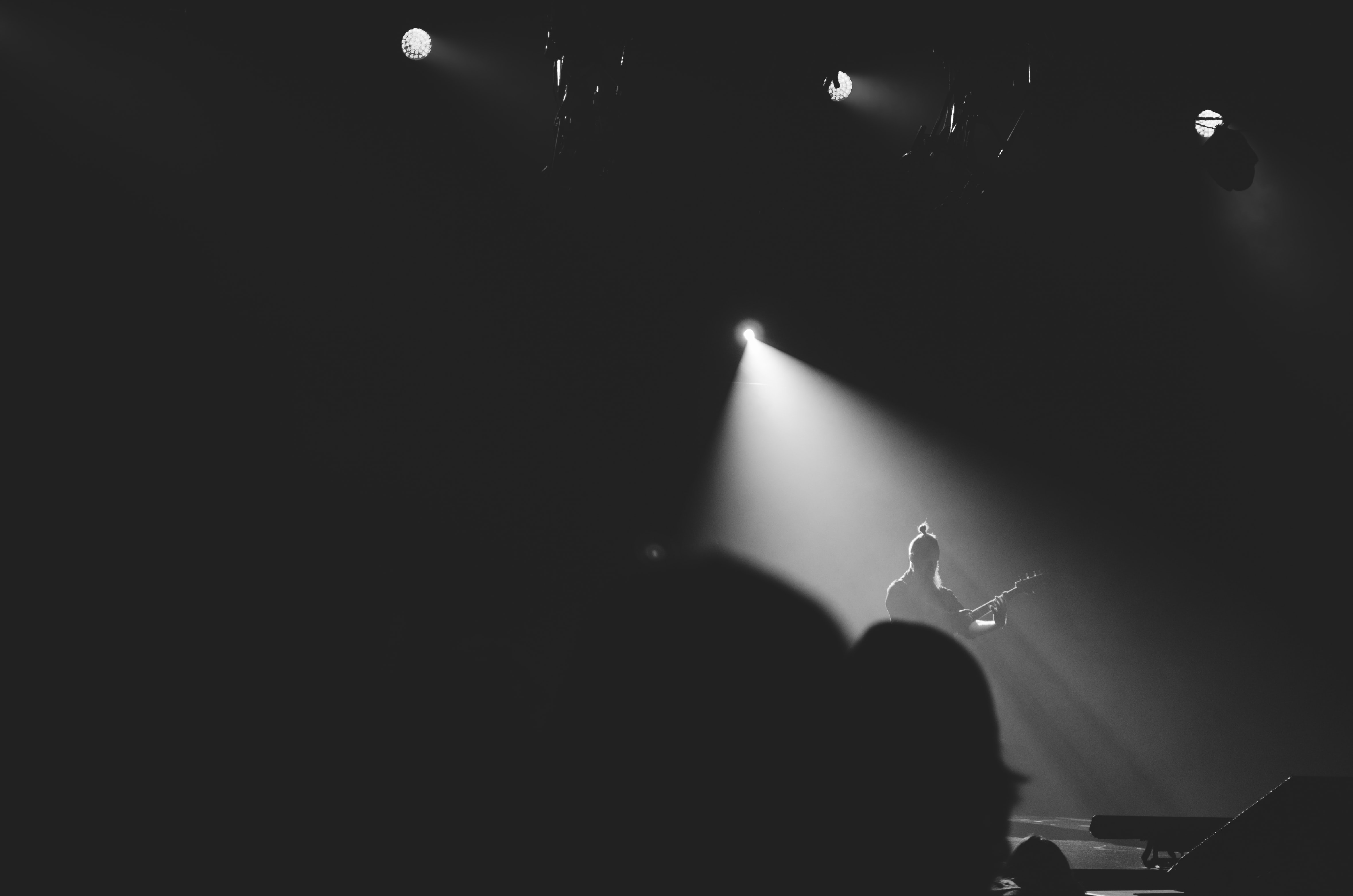 A guitar player illuminated by white floodlights in the middle of a dark stage