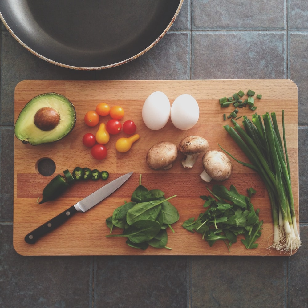 Flat lay of fresh ingredients with avocado, herbs, jalapeno, and egg