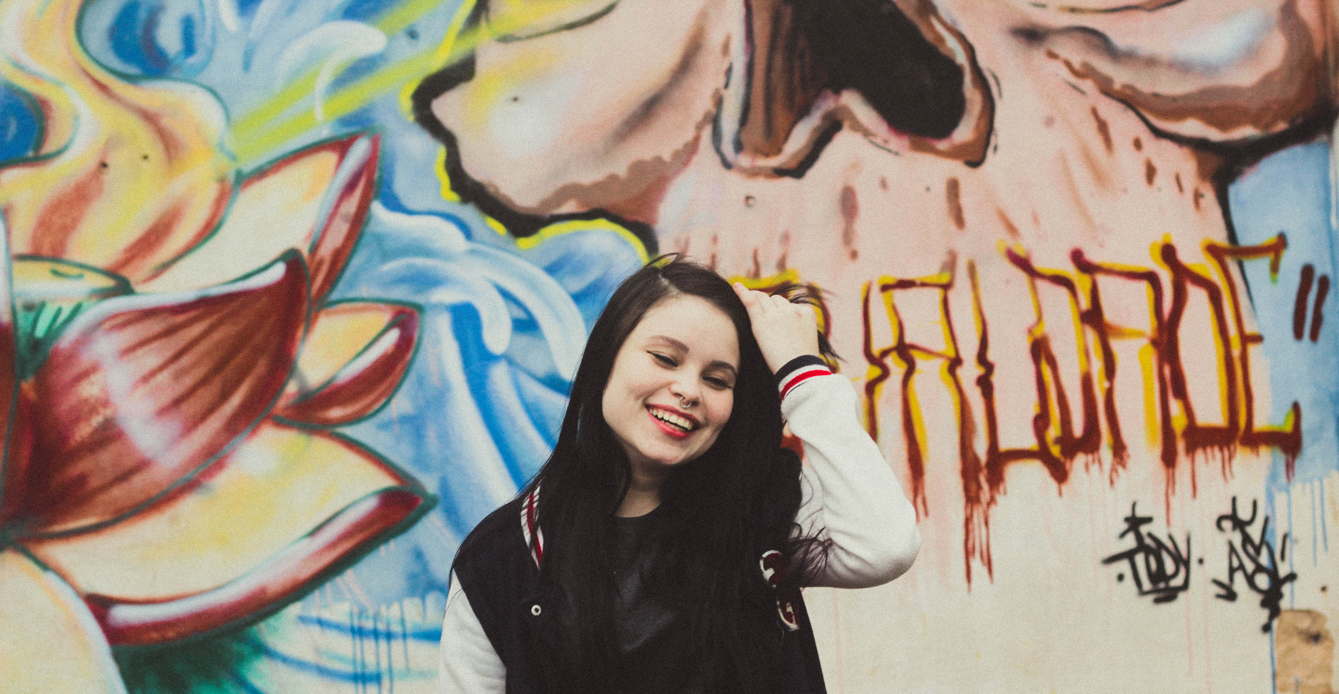 woman wearing black and white letterman jacket standing in front of mural painting