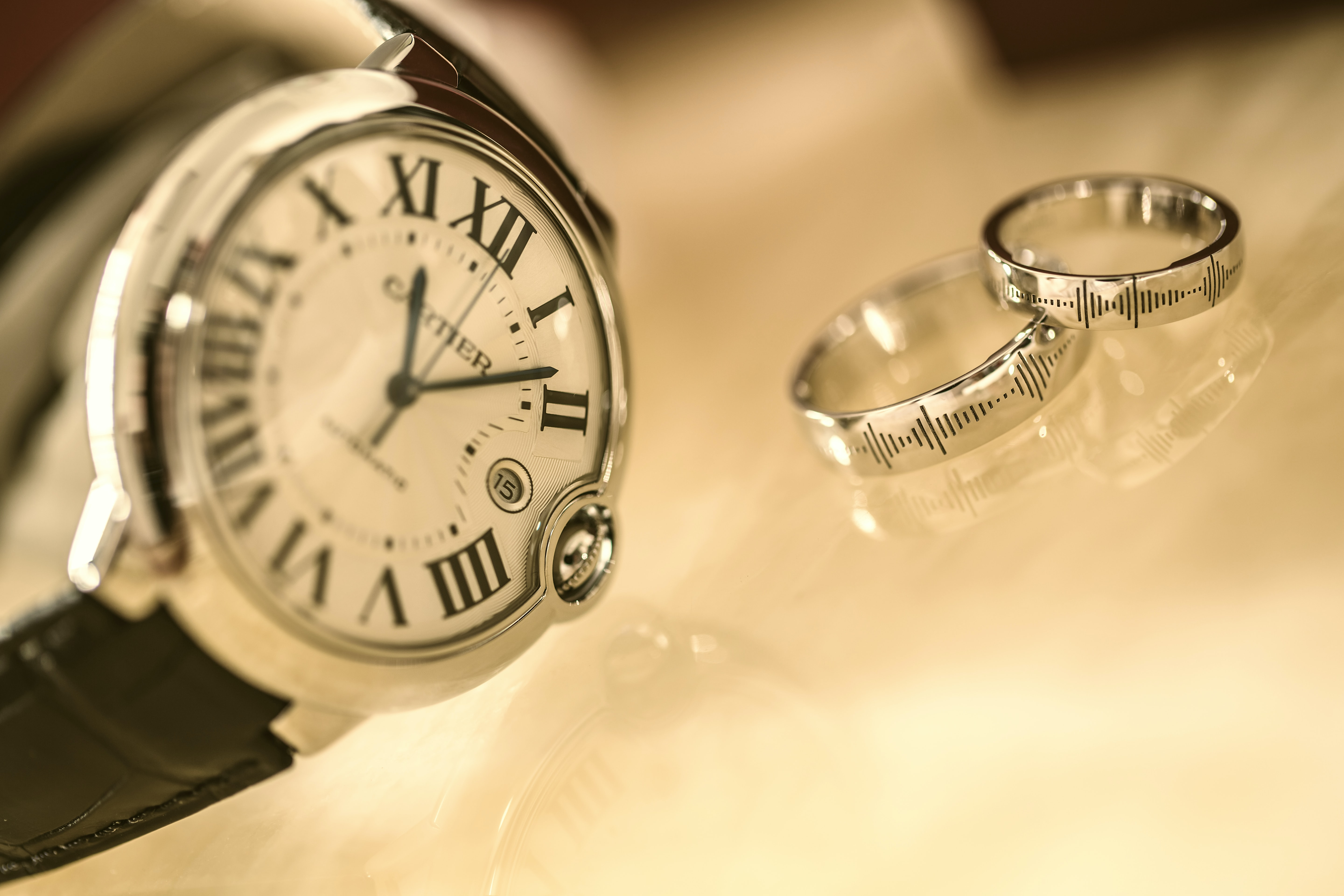 A watch with Roman numerals sits with wedding bands on clear surface in Tianjin