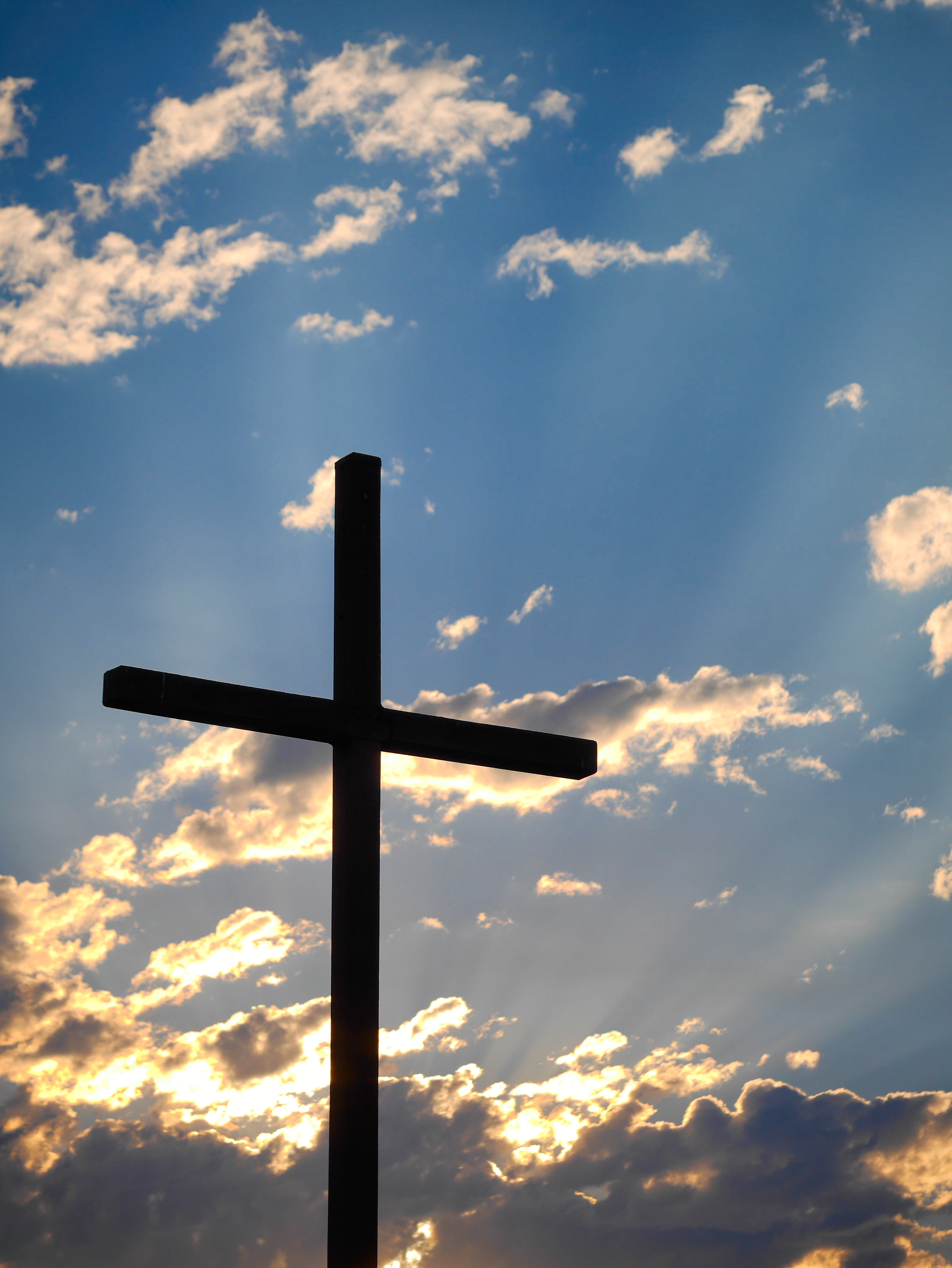 A large cross with a bright cloudy sky in the background.
