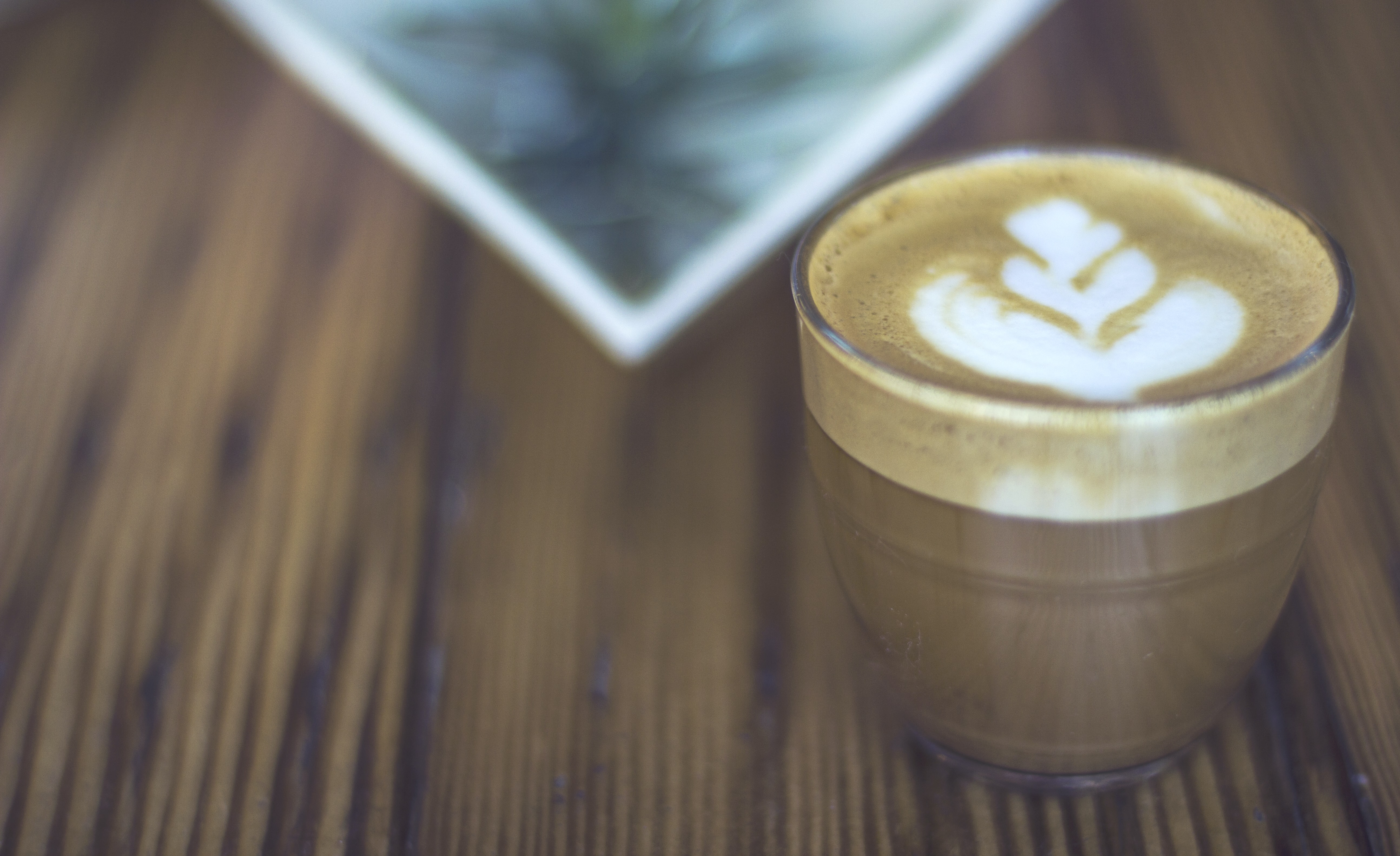 A cup of coffee with latte art in a glass on a wooden table in Cincinnati