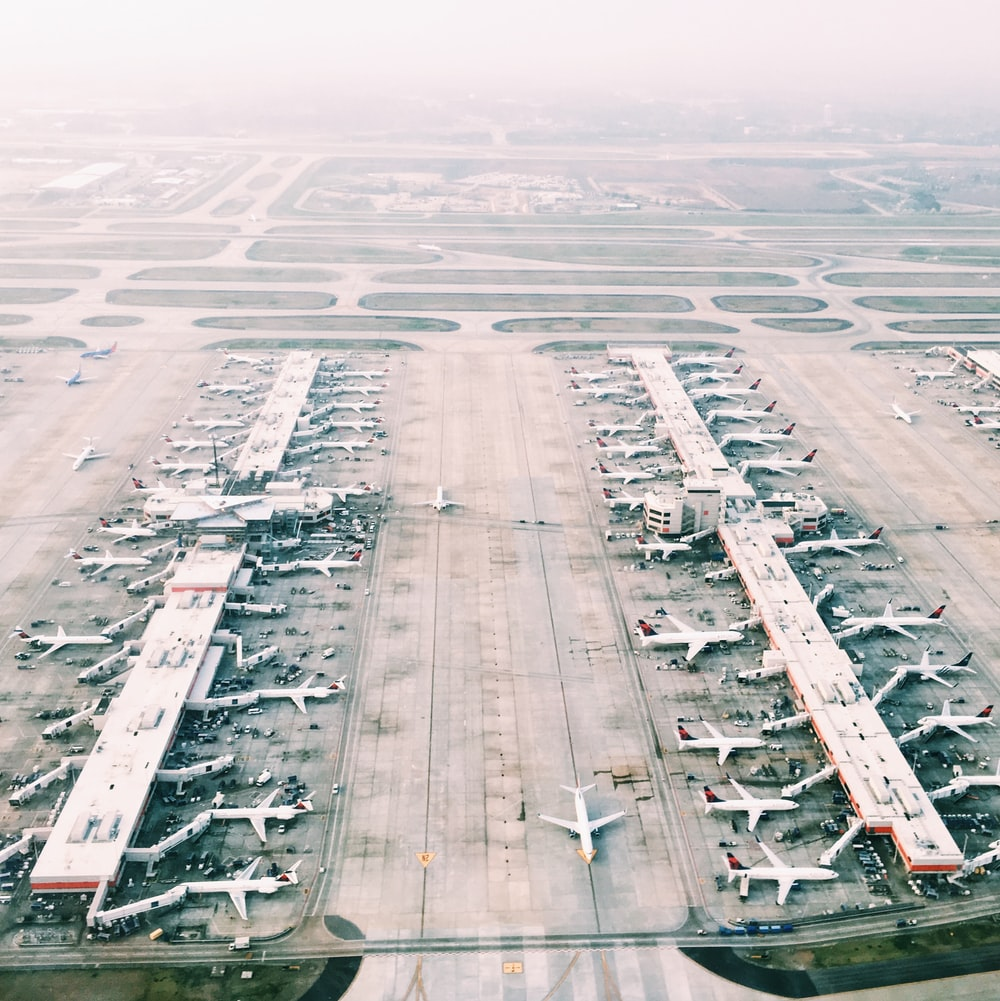 aerial view of airport with lots of airplanes during daytime