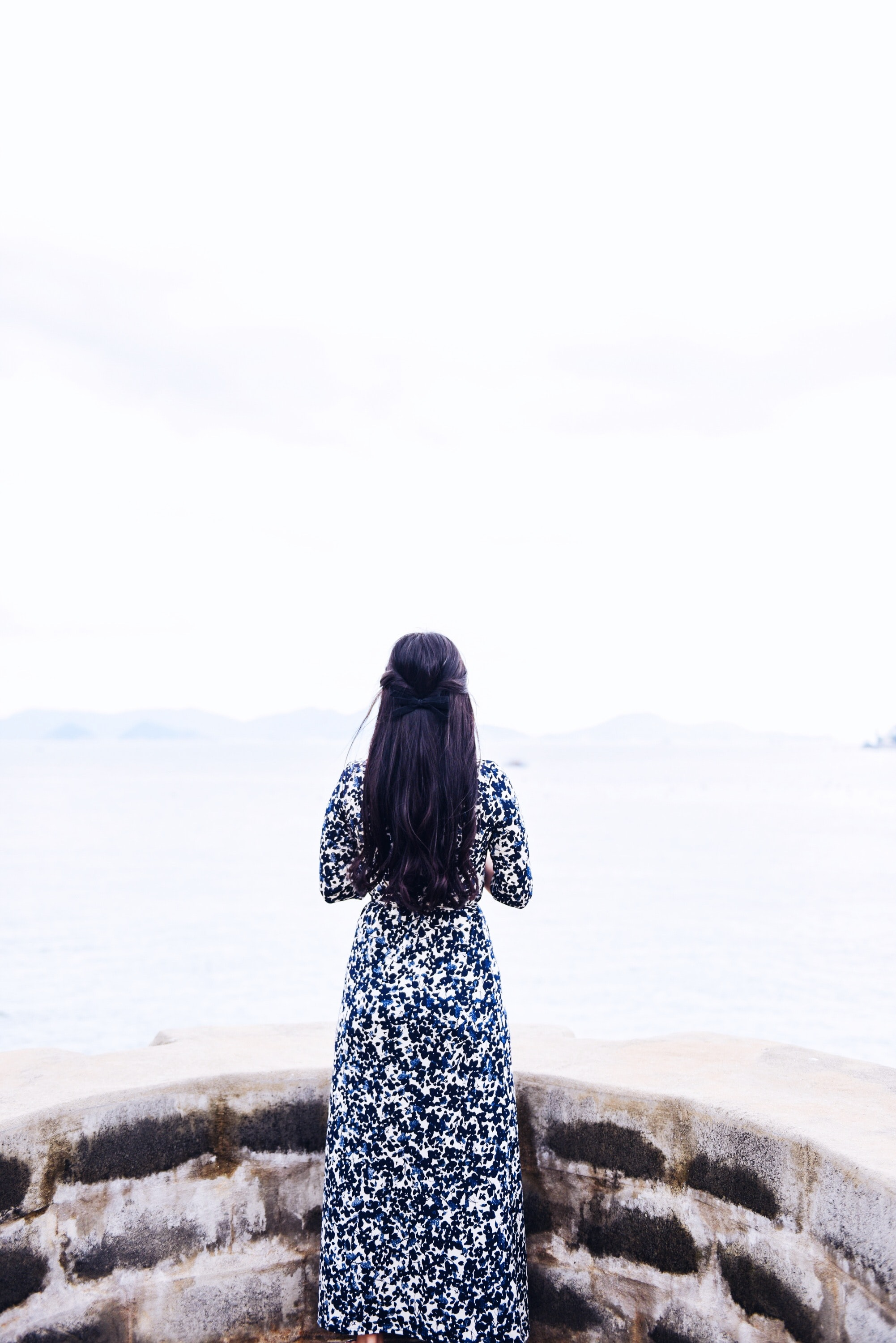 A woman in a dress standing steading next to a stone ledge and looking off into the sea