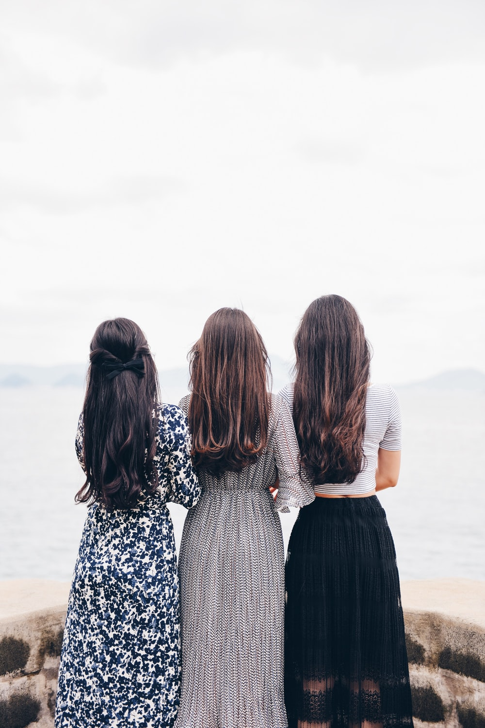 three woman looking back and facing body of water