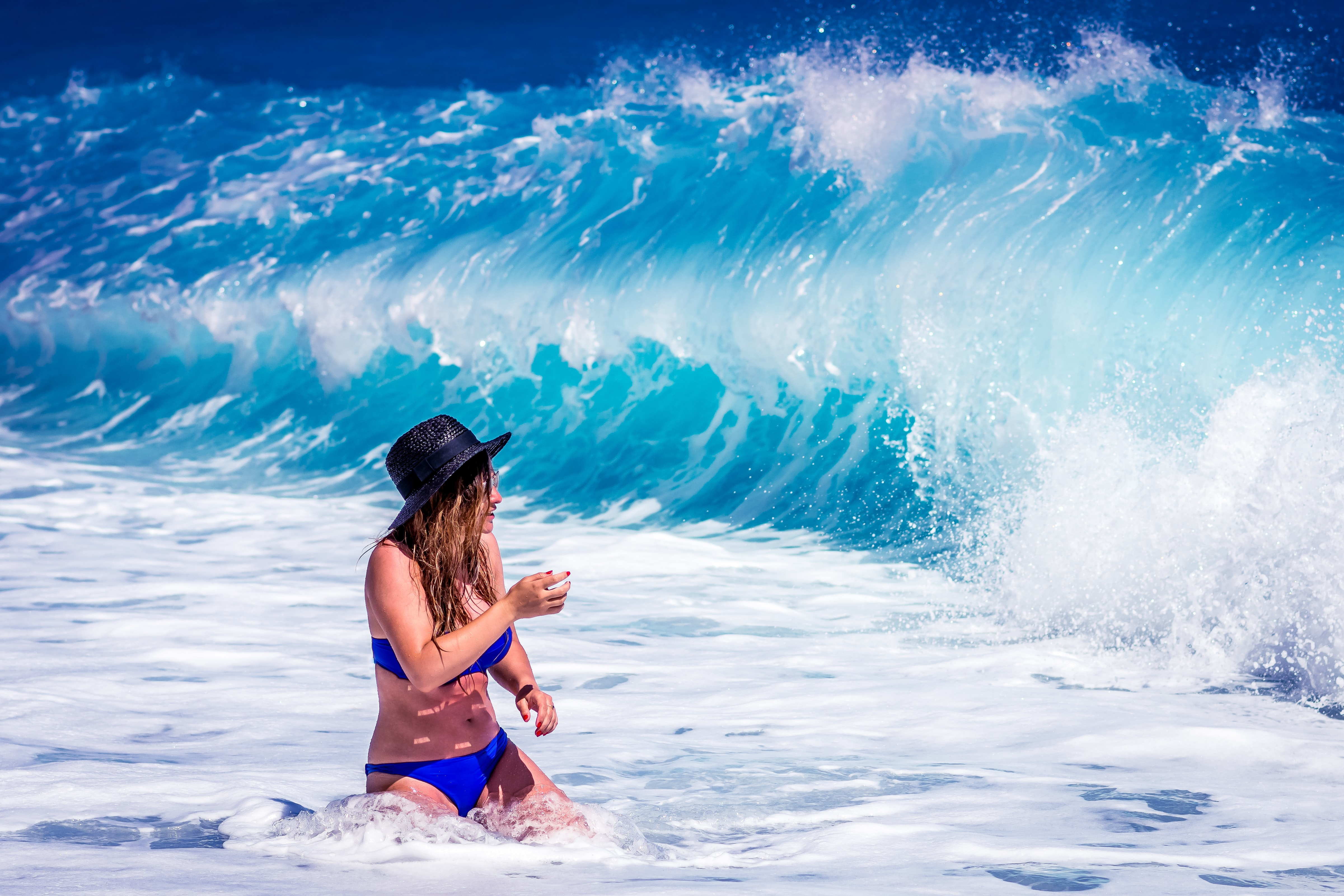 Woman in a swimsuit with a hat about to be splashed by the wave at Lalaria beach