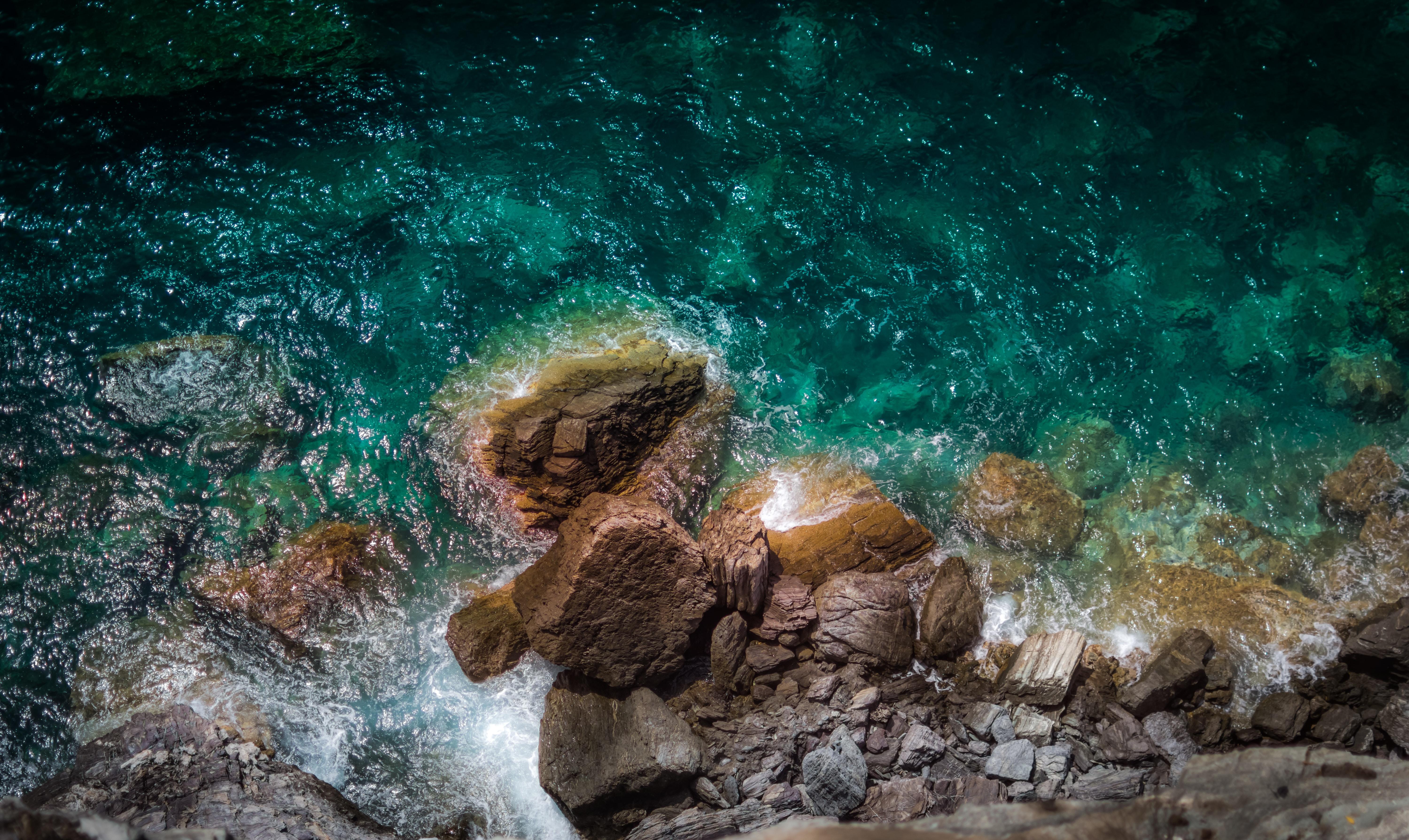 rocky shore near teal body of water