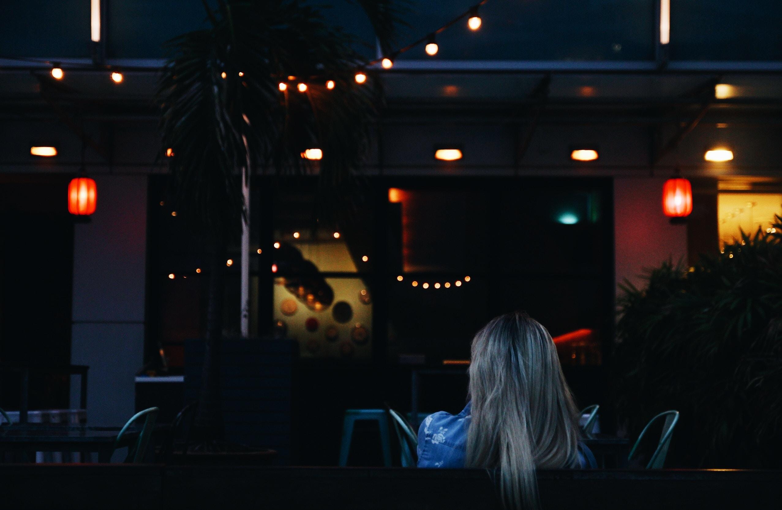 woman sitting while facing towards bar