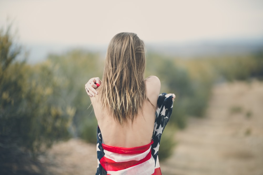 focus photography of half naked woman covering body with USA flag