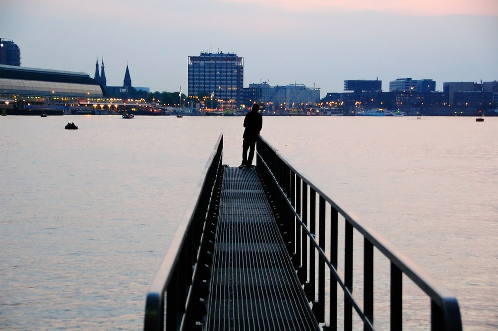silhouette of person standing on metal dock