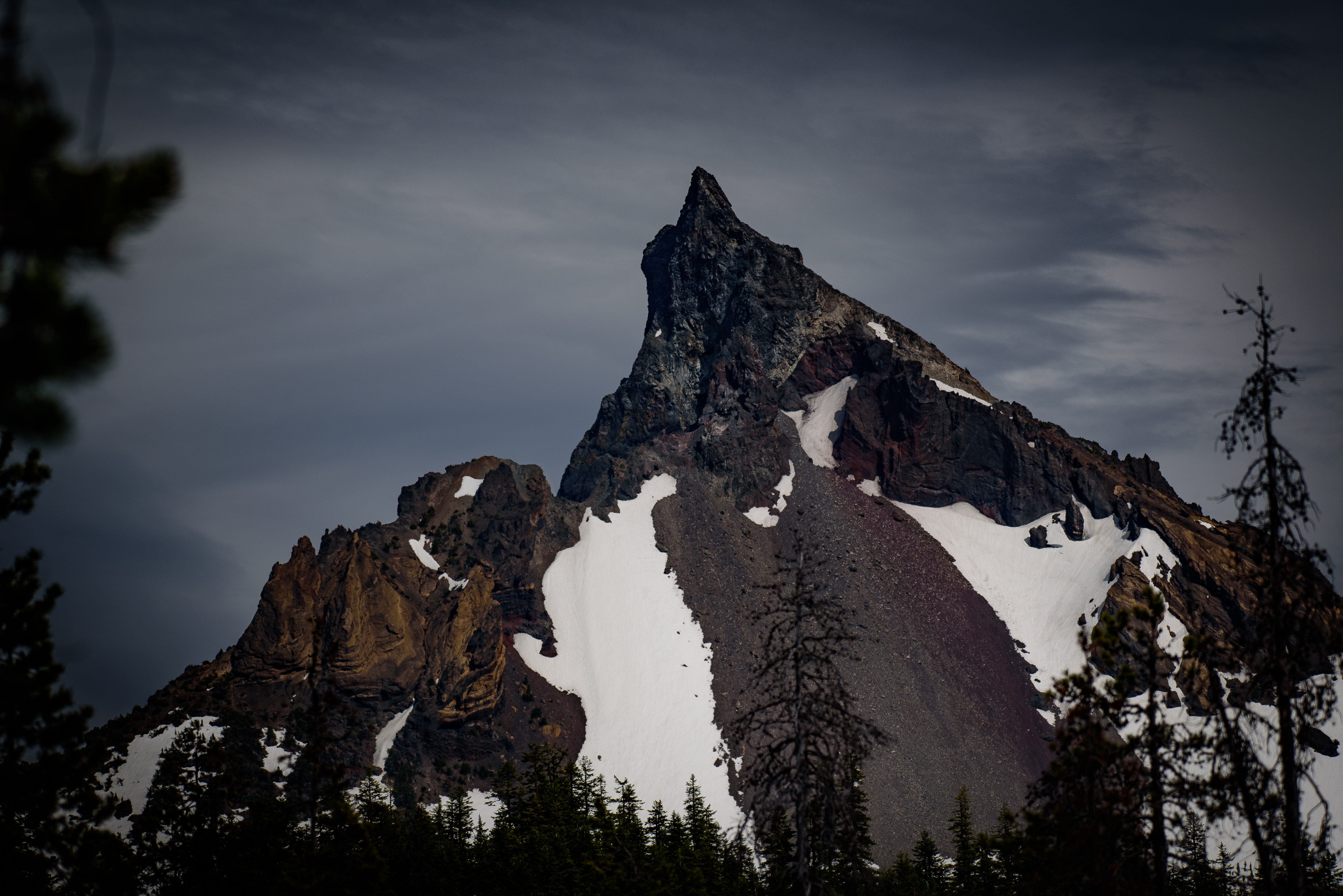 The rocky peak of a mountain covered partly in snow with trees in front
