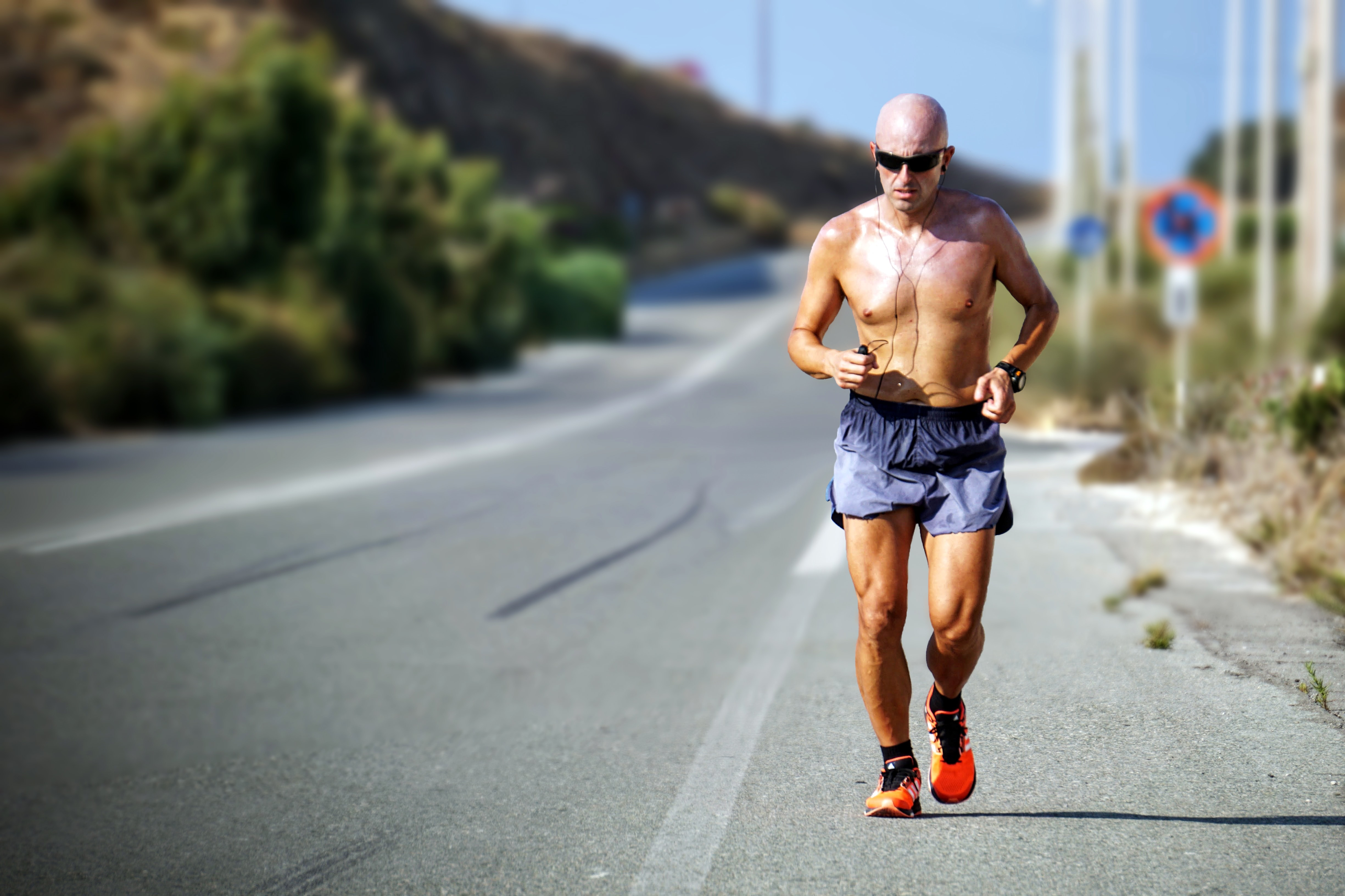 man jogging while listening using black earphones during day time